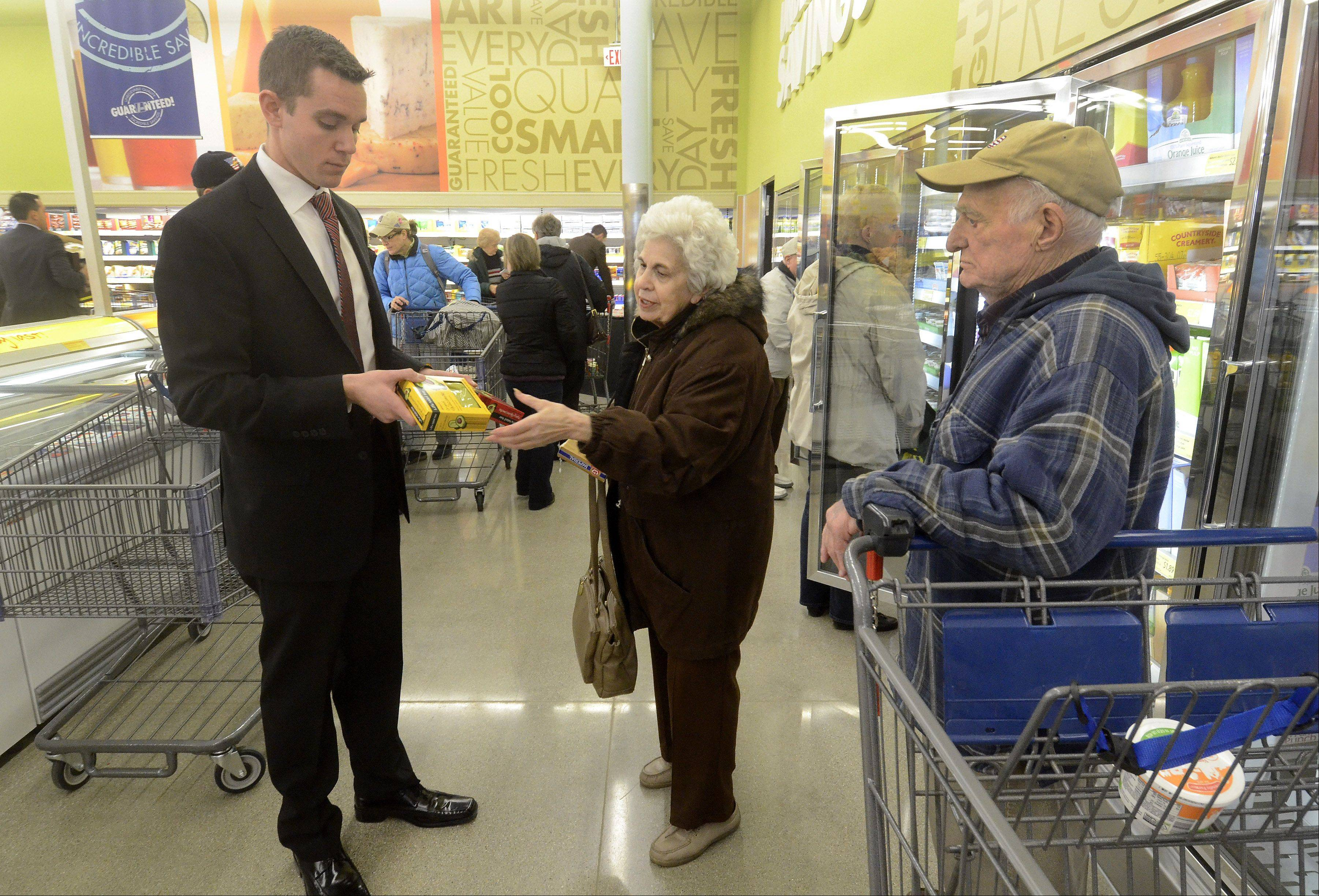 District Manager Zac Birkey helps out Joan and Anthony Gargano of Prospect Heights at the new Aldi grocery store that formally opened Thursday in Mount Prospect.