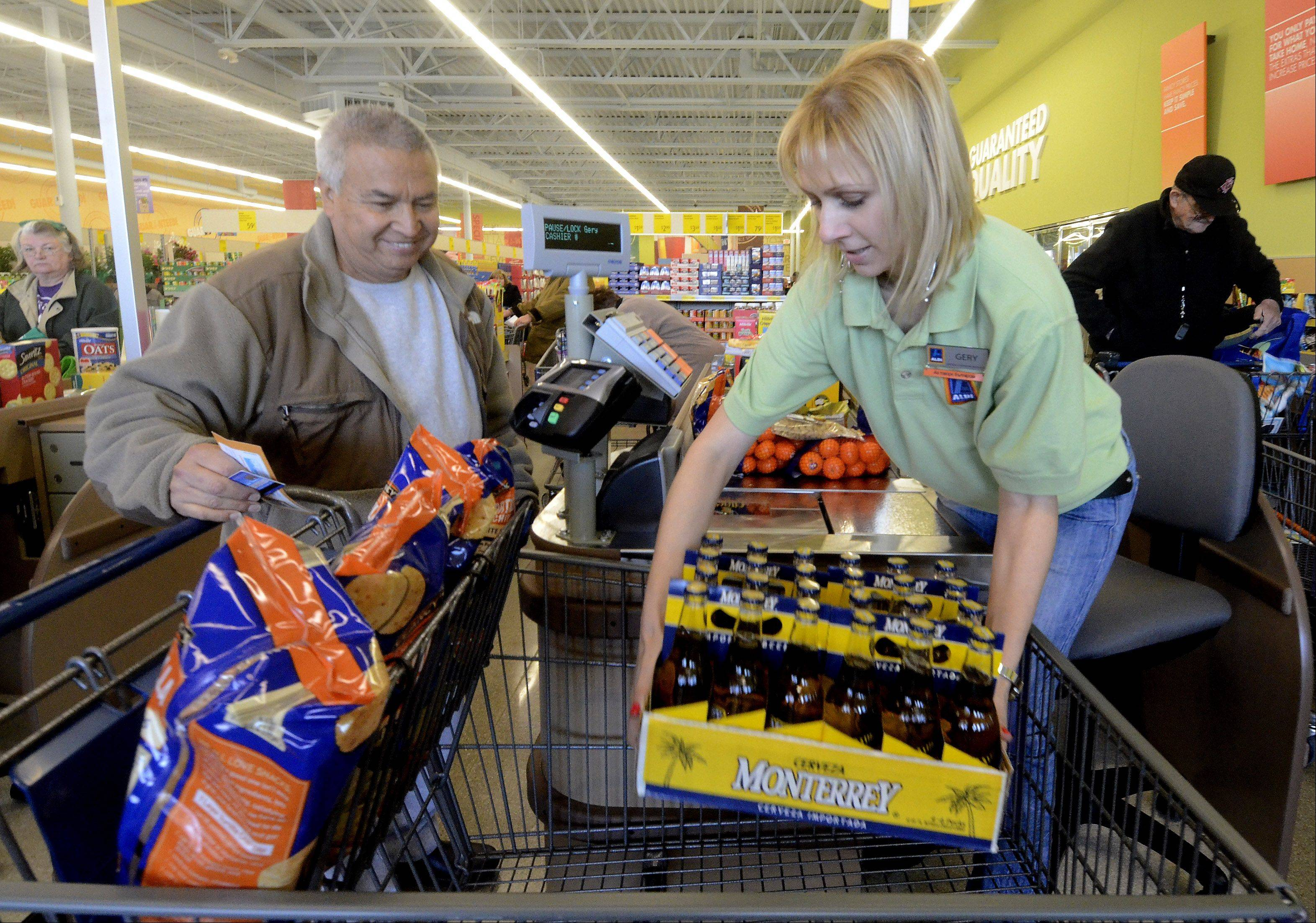 Cashier Gery Demitrova helps Salvador Ochoa to check out at the new Aldi grocery store which formally opened Thursday in Mount Prospect.
