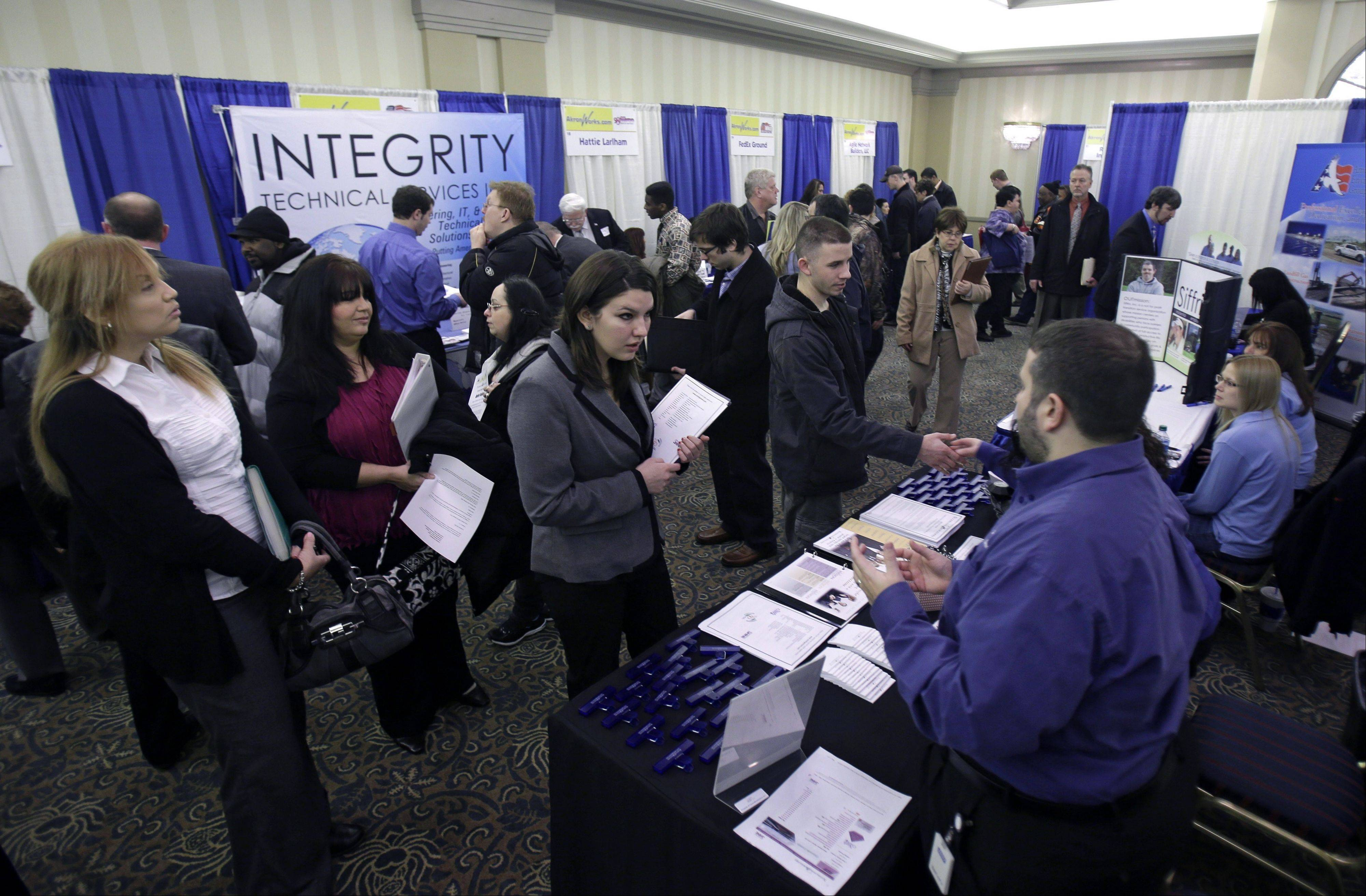 Job seekers meet with employers at a job fair in Sunrise, Fla.