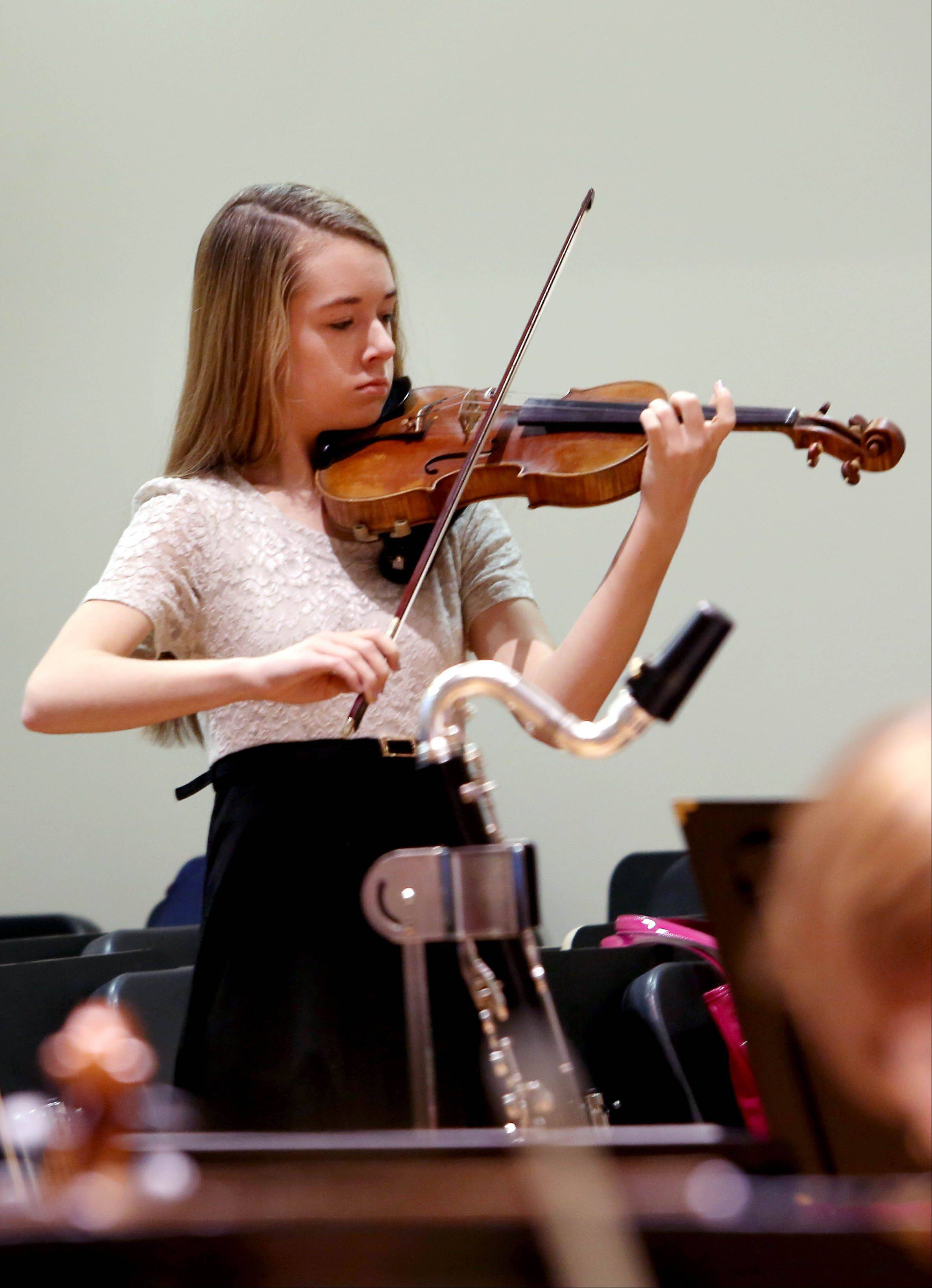 Serena Harnack, 14, of Glen Ellyn, warms up and she gets ready to practice her solo with the DuPage Symphony Orchestra at Wentz Hall in Naperville. She performed with the orchestra May 16 after winning a student competition.