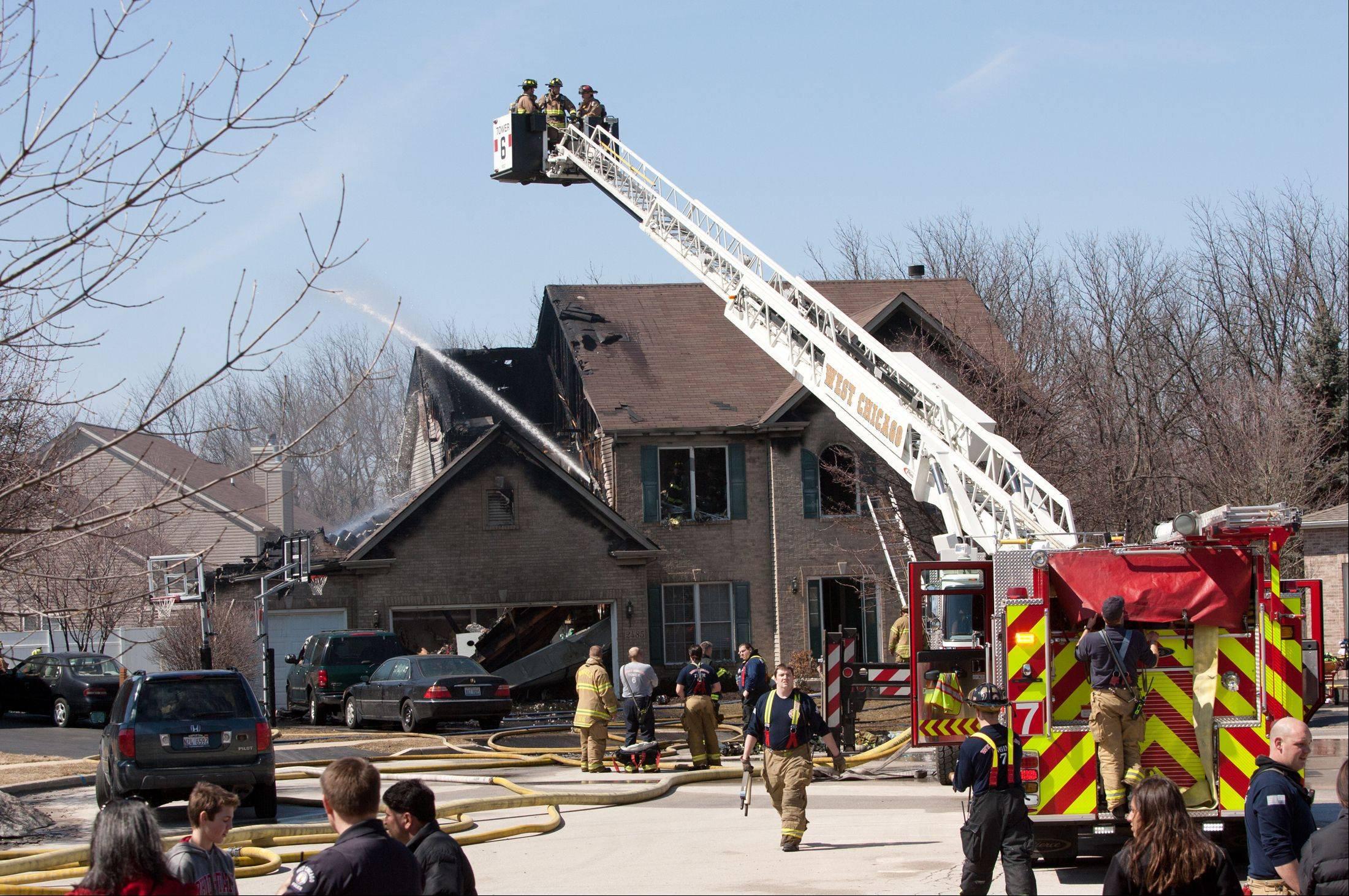 "West Chicago firefighters battle a house fire Thursday on the 2400 block of Alamance Drive that authorities said ""had a good head start"" before they were dispatched to the scene."