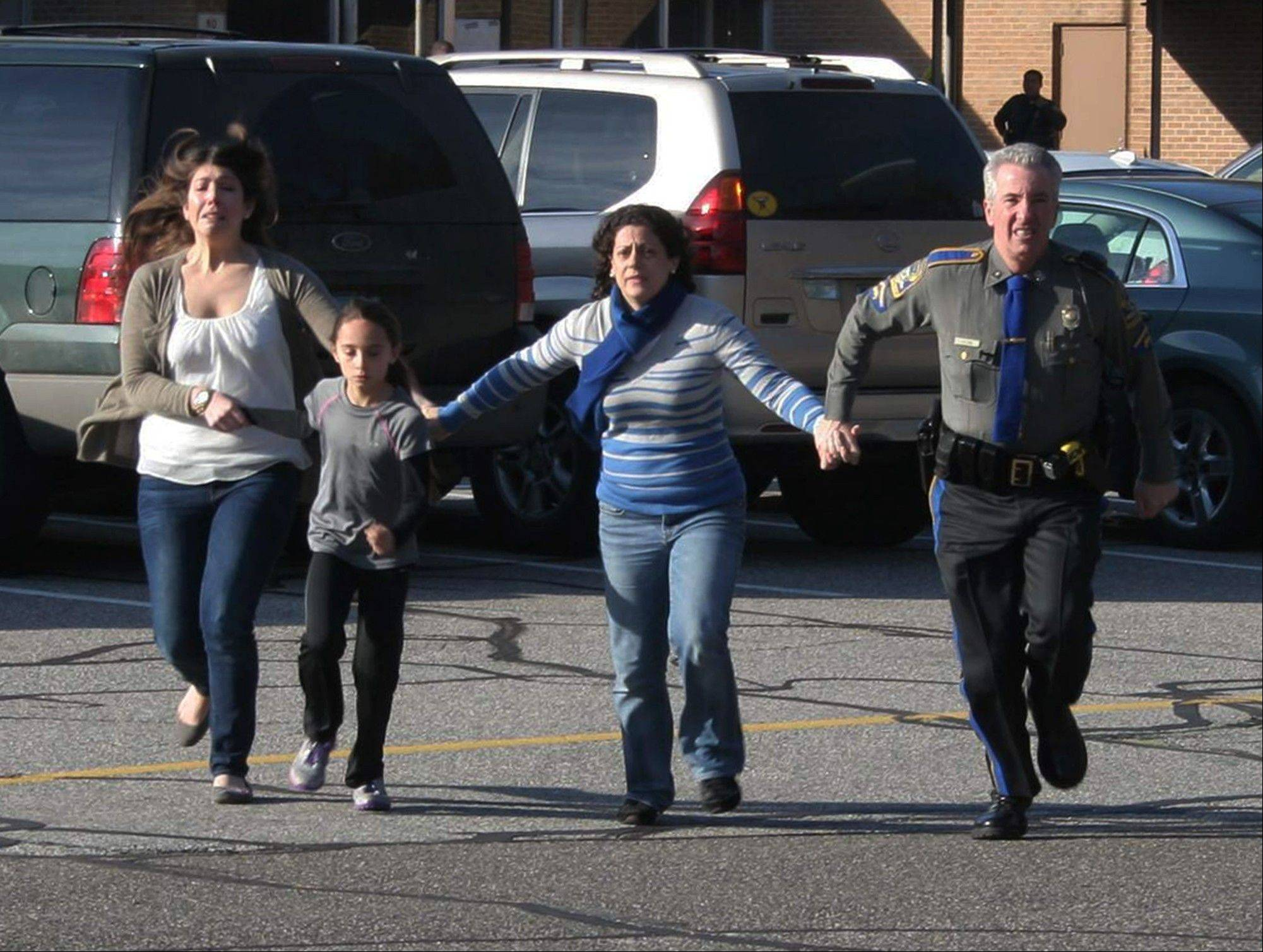 In this Dec. 14, 2012 e photo, a police officer leads two women and a child from Sandy Hook Elementary School in Newtown, Conn., shortly after Adam Lanza opened fire, killing 26 people, including 20 children.