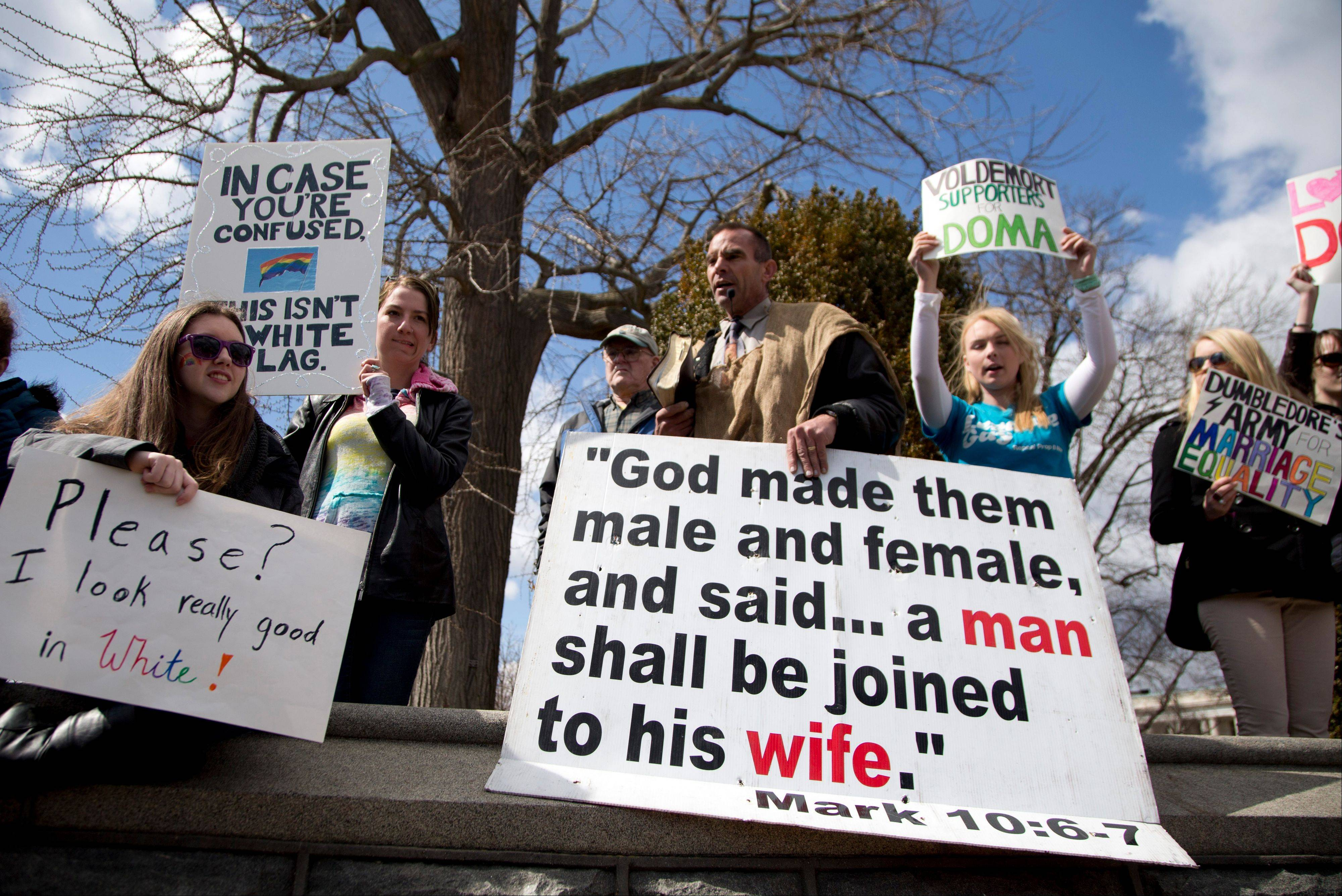 Allan Hoyle of North Carolina, with the large white sign, center, speaks out against gay marriage across from the street from the Supreme Court in Washington, Wednesday.