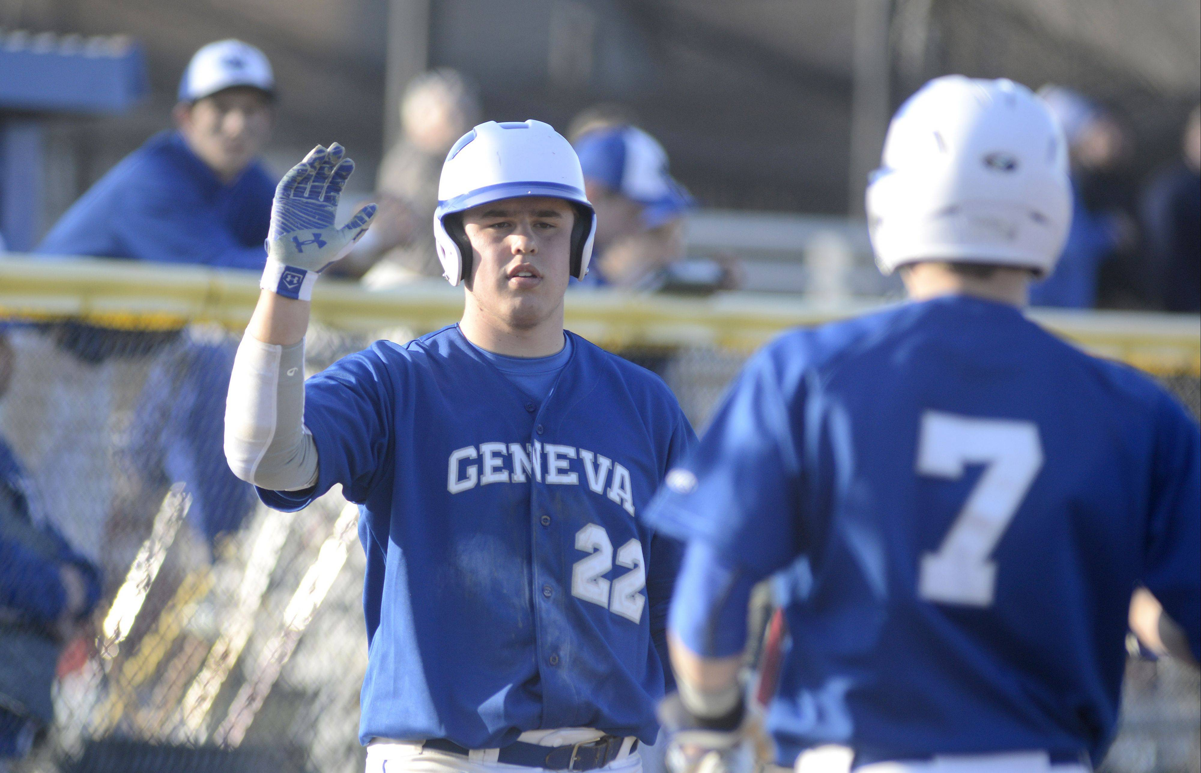 Above: Geneva's Anthony Bragg greets Nick Derr on the way back to the dugout after scoring a run in the sixth inning on Thursday in Geneva. Below: Marmion's RJ Gibson bolts to third base trying to beat the throw to Geneva's Mitchell Endriukaitis.
