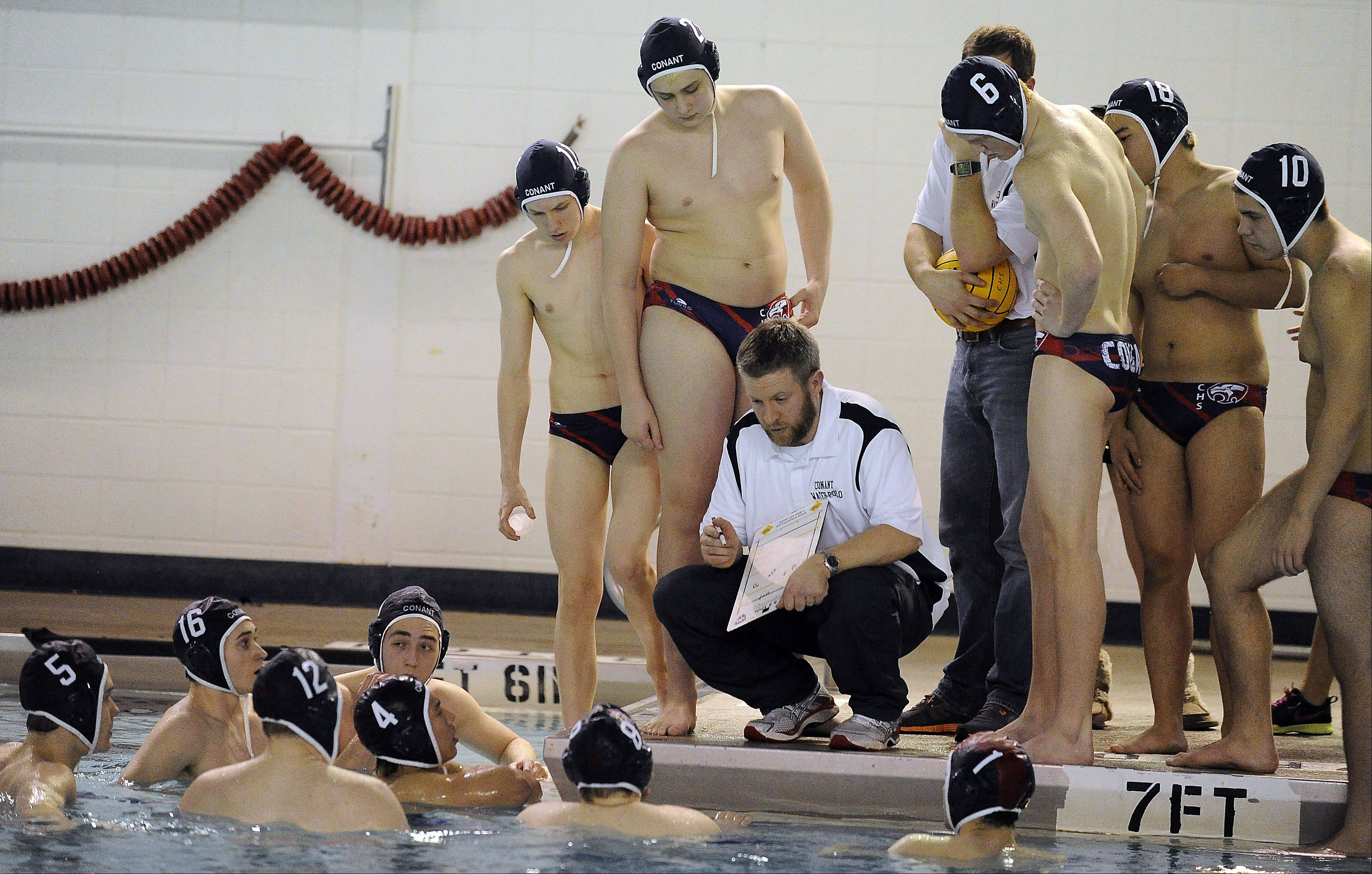 Conant boys water polo coach Tim Daniel talks to his players at a recent game.