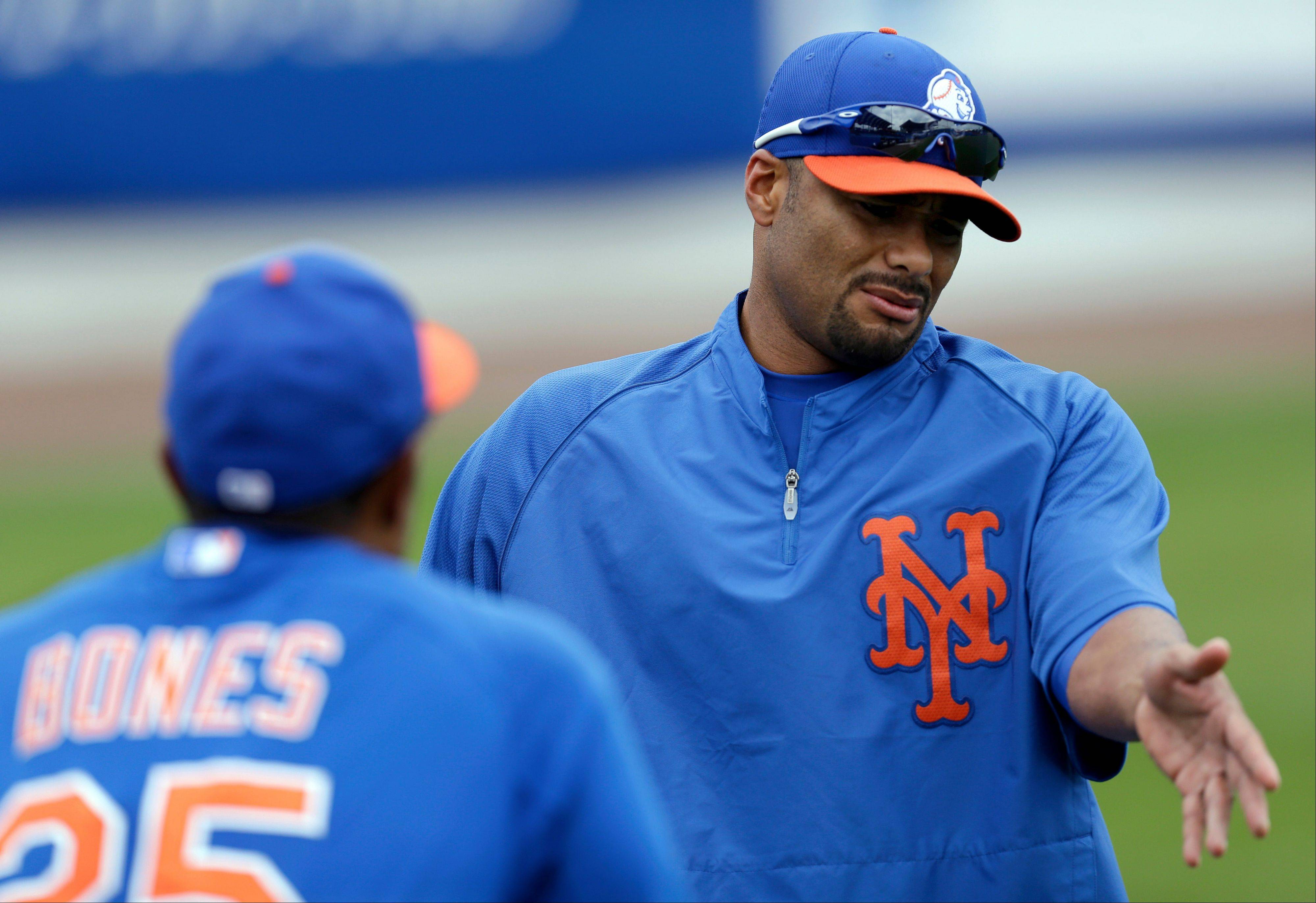 In this March 1, 2013, photo, New York Mets pitcher Johan Santana, right, talks to bullpen coach Ricky Bones (25) before the Mets' spring training baseball game against the Detroit Tigers in Port St. Lucie, Fla. The Mets say Santana has injured his left shoulder again and likely will need surgery and miss the 2013 season.
