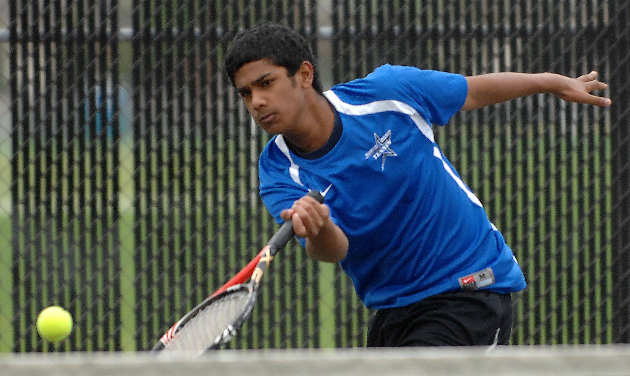 St. Charles North's Dominick Amalraj rushes for a ball at the net in the second singles finals during Saturday's Upstate Eight Conference Tournament at Streamwood.