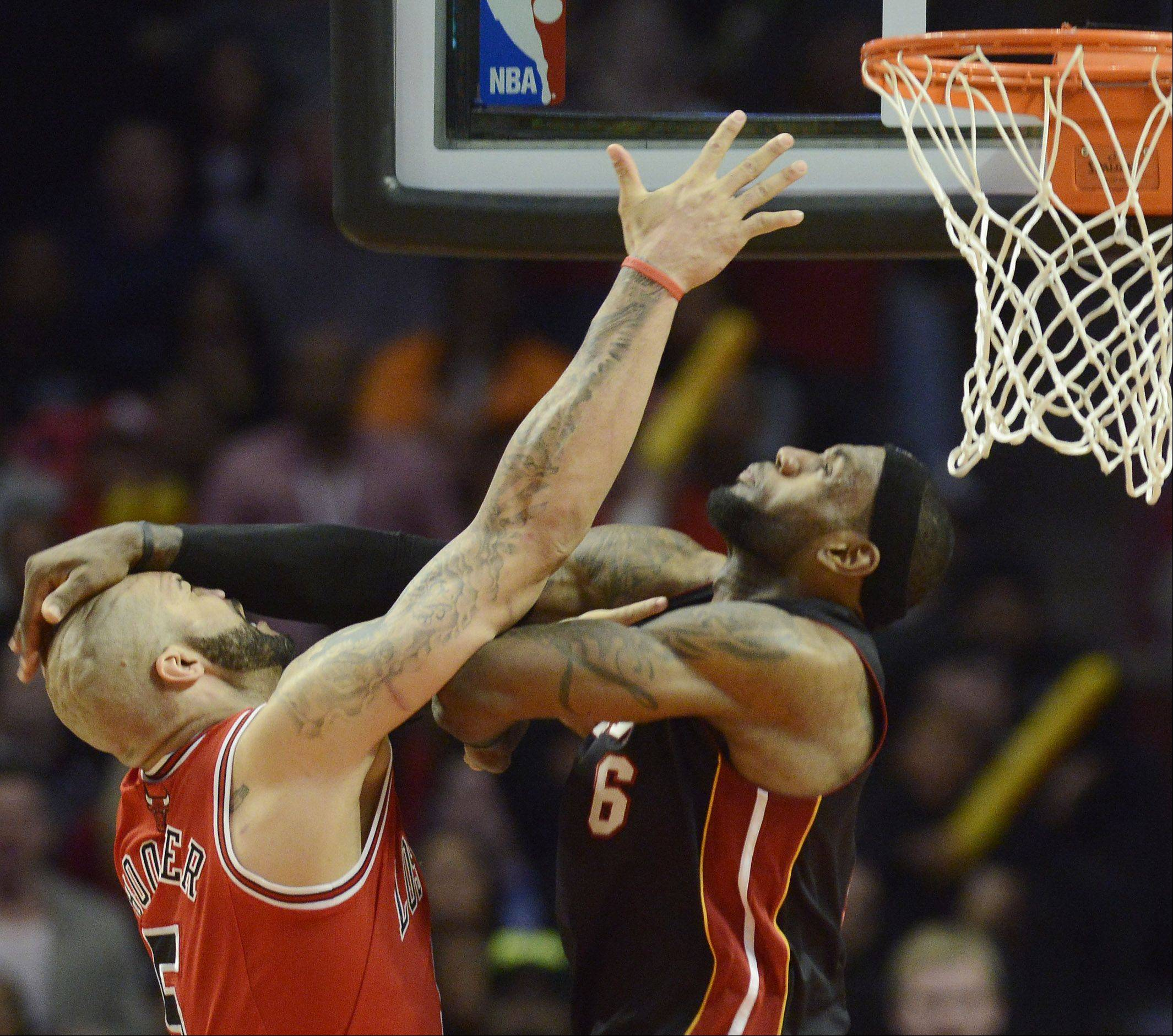 Carlos Boozer of the Bulls and LeBron James of the Heat make contact under the basket.