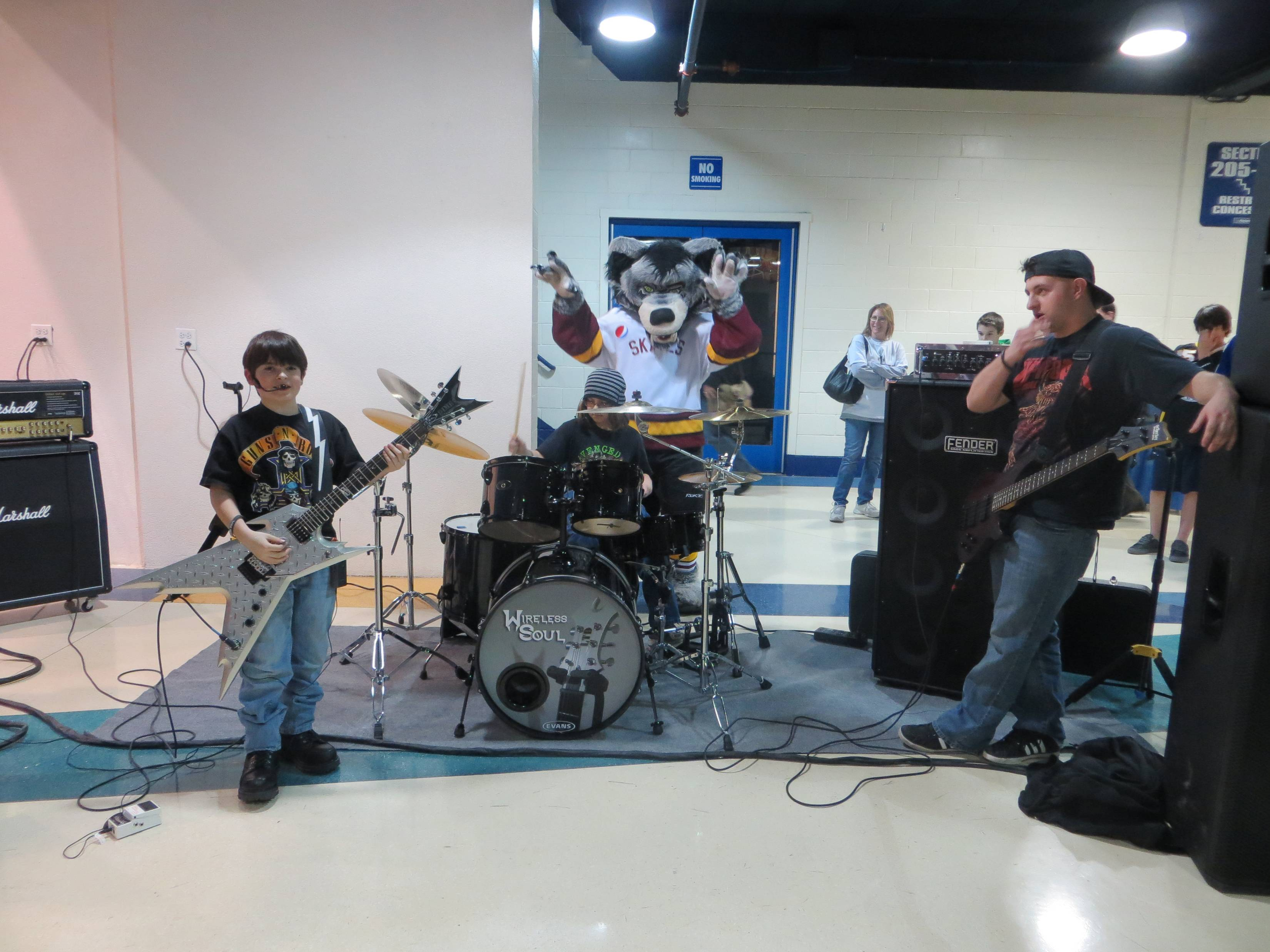Vince Minogue (left) lead vocals and guitar and Joe Cangelosi (center) drums and vocals of Wireless Soul featuring Brad Opalinski on bass with Skates (the official mascot of The Chicago Wolves) at Allstate Arena.