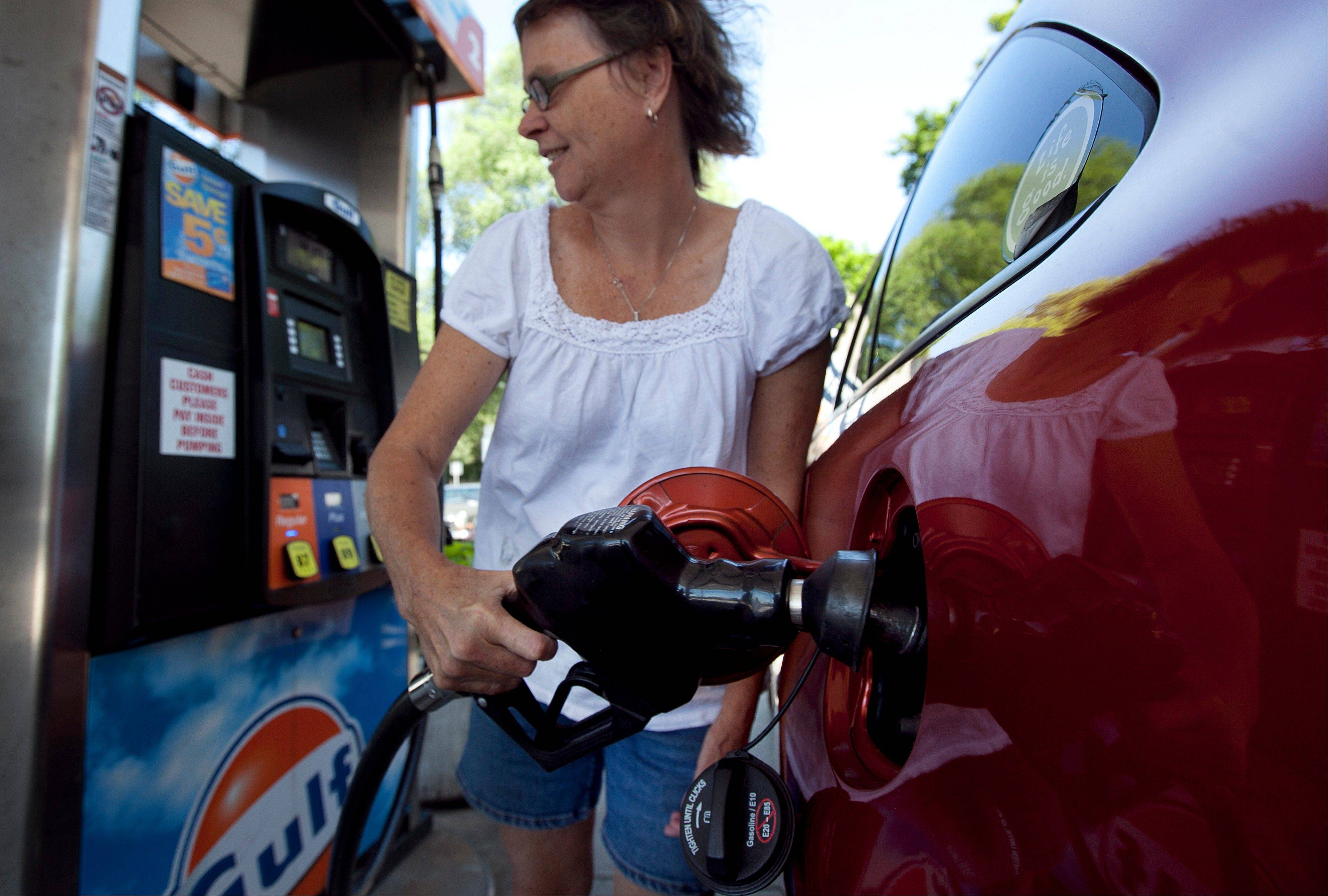Suzanne Meredith of Walpole, Mass., gases up her car at a Gulf station in Brookline, Mass. Reducing sulfur in gasoline and tightening emissions standards on cars beginning in 2017, as the Obama administration is proposing, would come with costs as well as rewards.