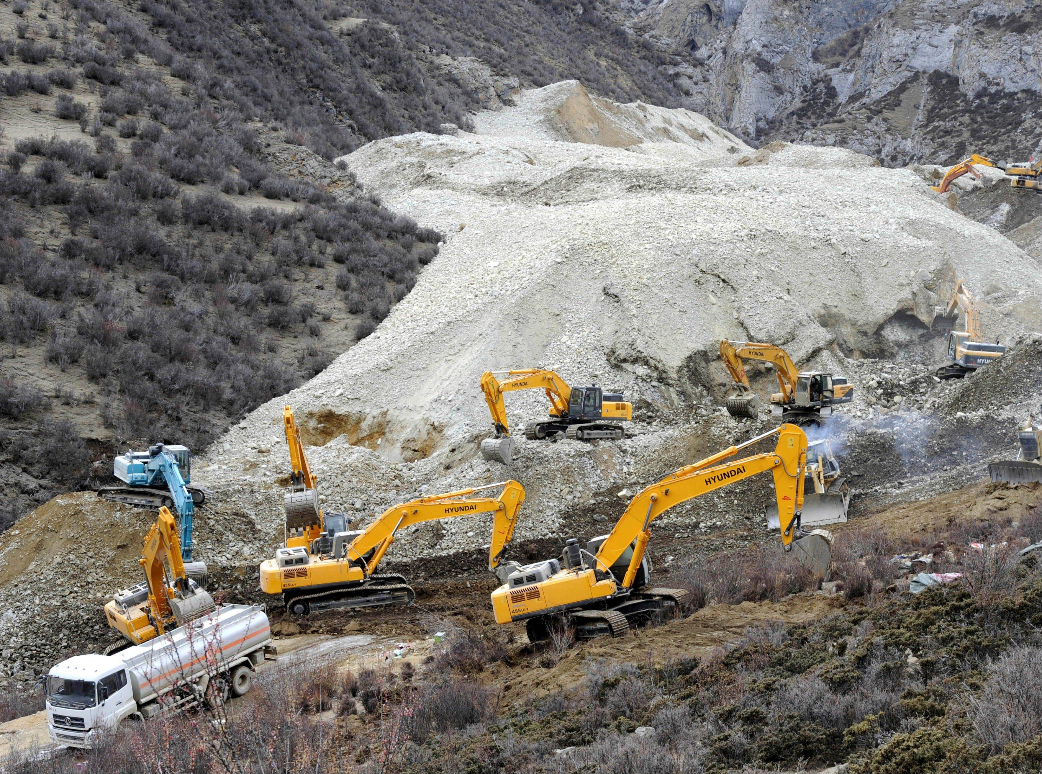 Earthmovers remove rocks and mud on the scene where a landslide hit a mining area in Maizhokunggar County of Lhasa, southwest China.
