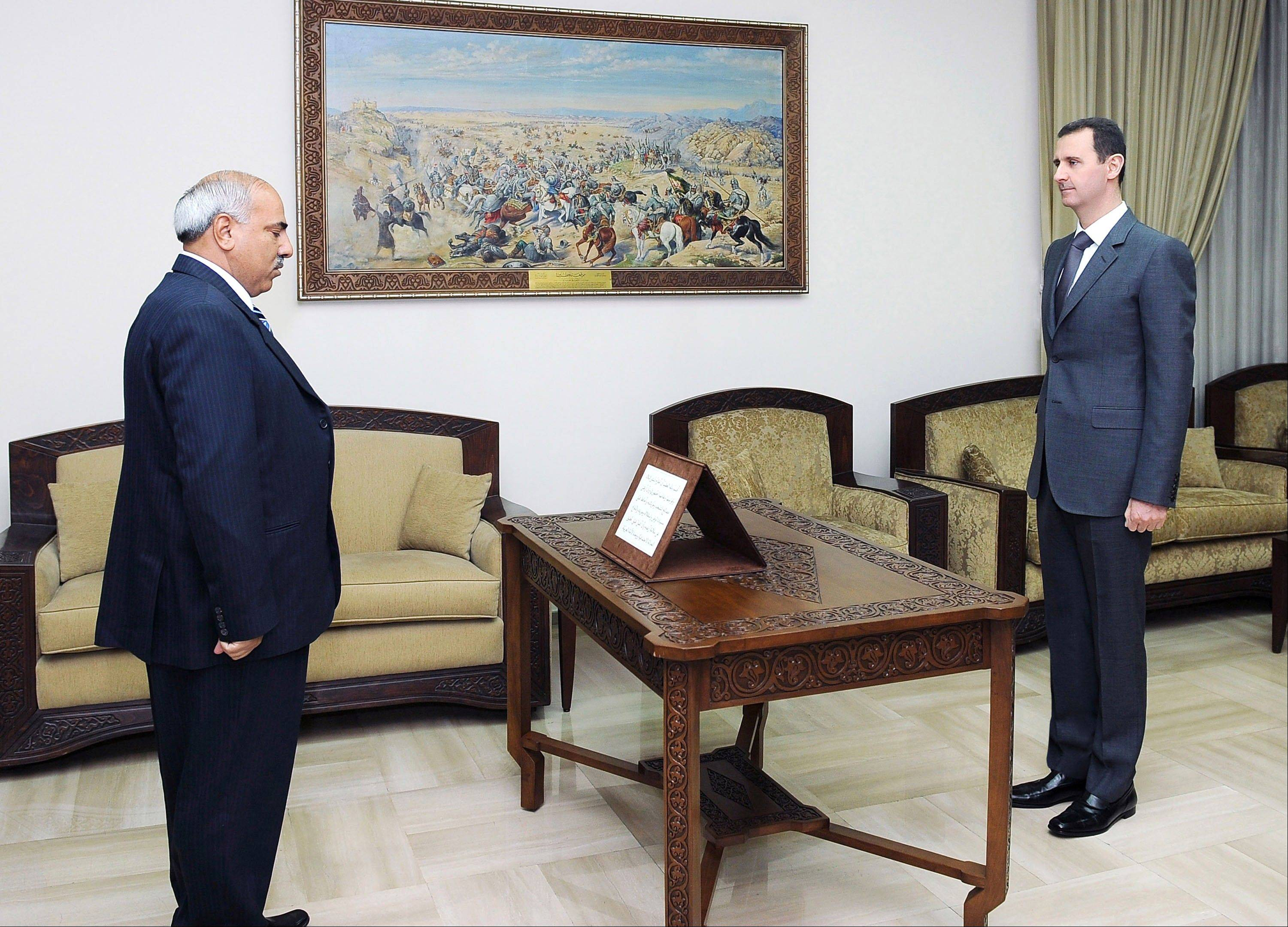 In this photo released by the Syrian official news agency SANA, Mohammed Zaal al-Ali, left, is sworn in Thursday as governor of Hasaka province by Syrian President Bashar Assad, right, in Damascus, Syria.