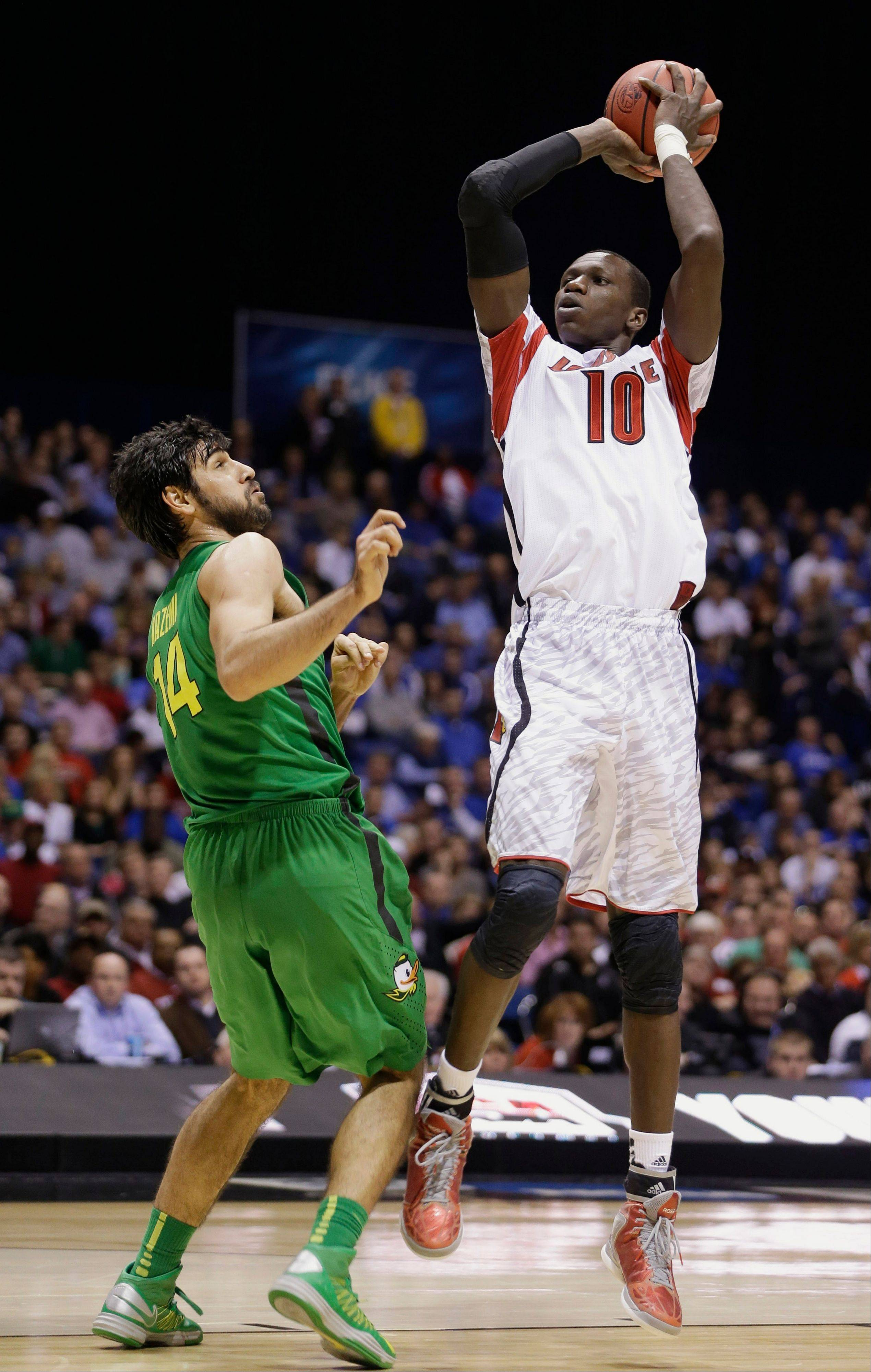 Louisville center Gorgui Dieng (10) shoots over Oregon forward Arsalan Kazemi (14) during the second half of a regional semifinal in the NCAA college basketball tournament, Friday, March 29, 2013, in Indianapolis. (AP Photo/Darron Cummings)
