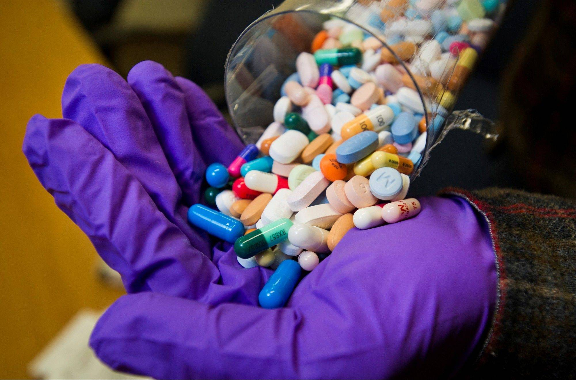 Police Department Detective Chris Couch empties a vial of prescription drugs, mostly painkillers, at the Columbus, Ind., station. Police acknowledge that the fight against drug abuse, especially the illicit use of prescription drugs, might never be fully won, but they insist that educational efforts and greater cooperation taking place among police agencies, doctors, hospitals and other medical professionals can save lives and lead to more arrests of dealers peddling painkillers.