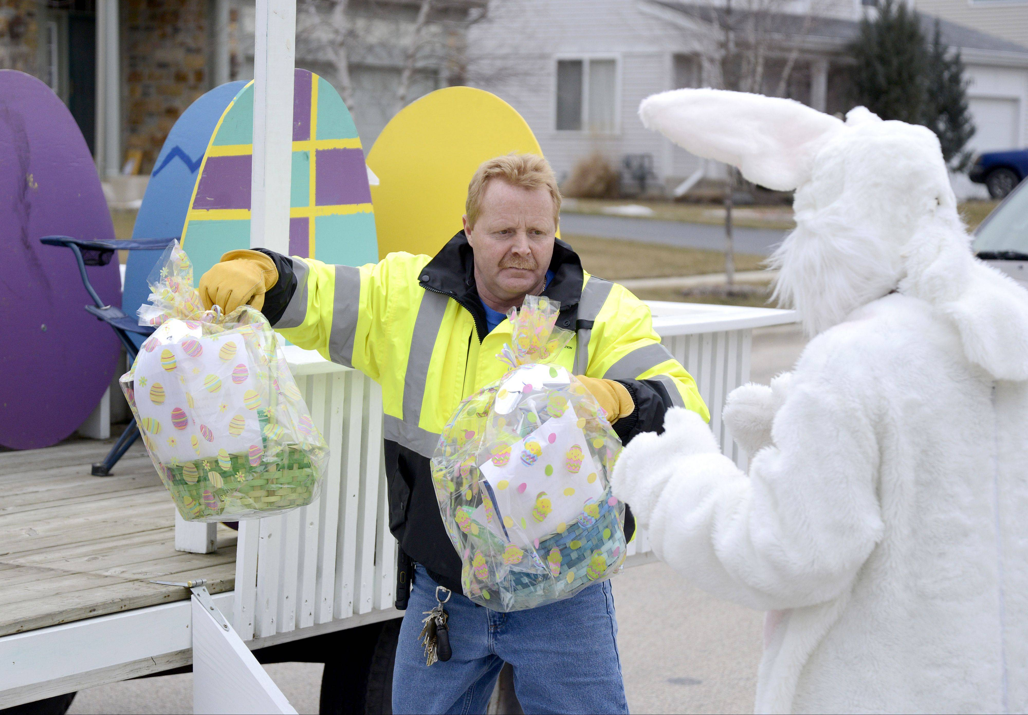 John Tyree hands off the baskets for the next delivery to the Easter Bunny (aka Tessa Eggebrecht of South Elgin). The South Elgin Parks and Recreation Department visited several homes recently making deliveries to children's front doors.