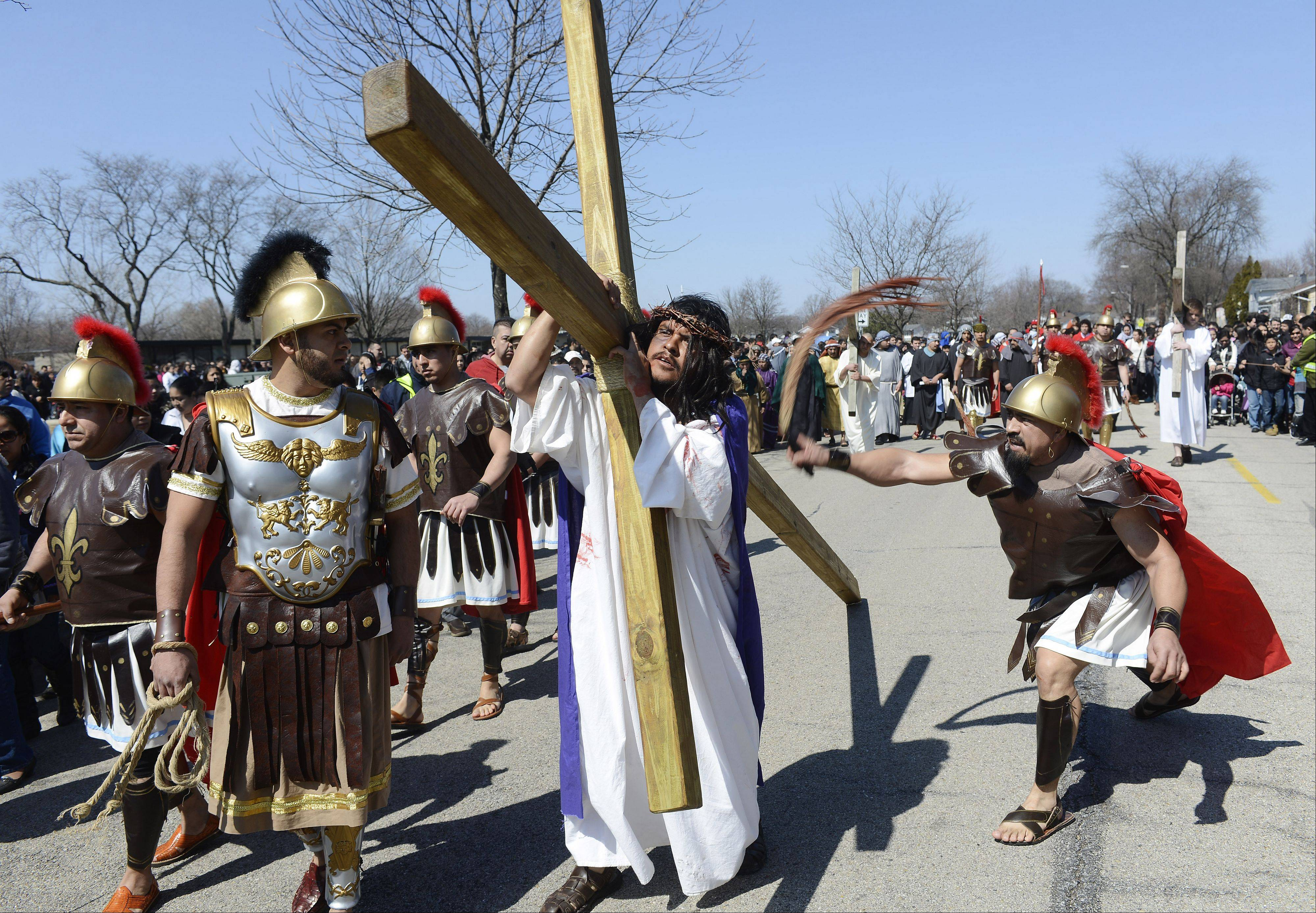 Jesus, played by Omar Palma, is whipped as he carries his cross during the Mision San Juan Diego Passion walk from St. Thomas of Villanova Church in Palatine on Good Friday.