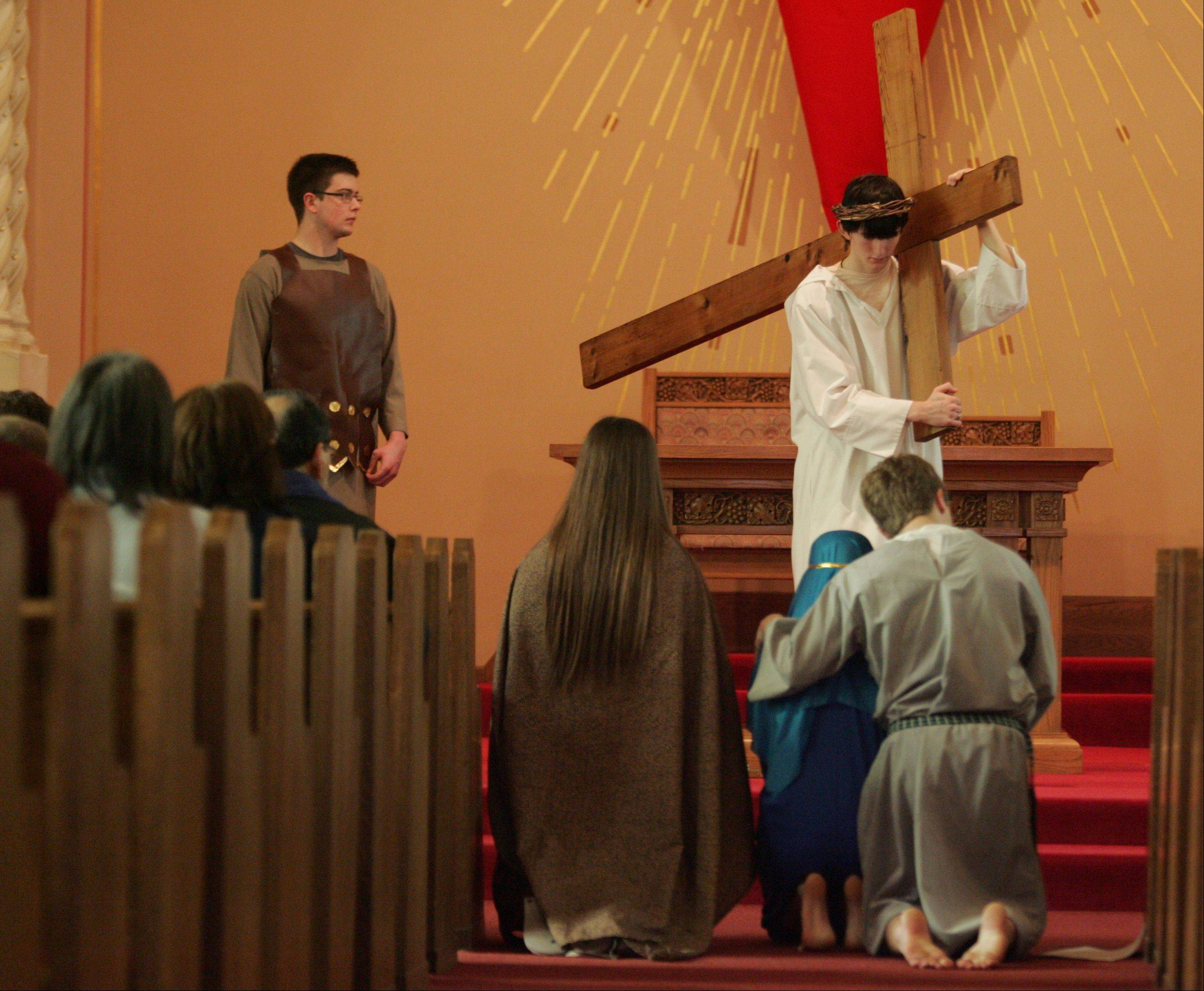 T.J. Foley, 18, portrays Jesus as Nick Wielgos, 19, looks on as a Roman soldier during a living stations of the cross Friday afternoon at St. Gall Catholic Church in Elburn. Both are from Elburn. The youth group at the church put the program together.