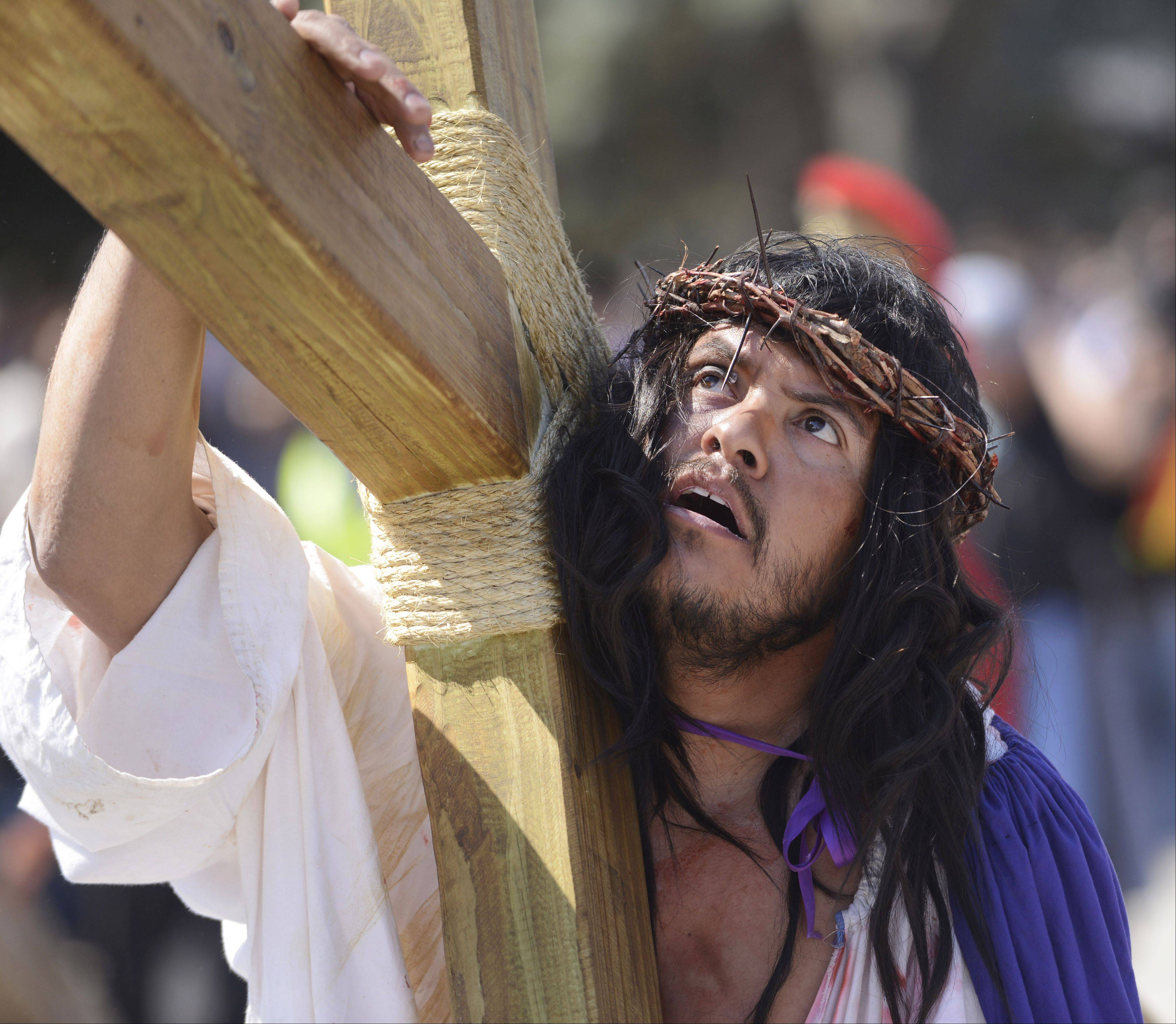 Jesus, played by Omar Palma, carries his cross during the Mision San Juan Diego Passion walk on Good Friday.