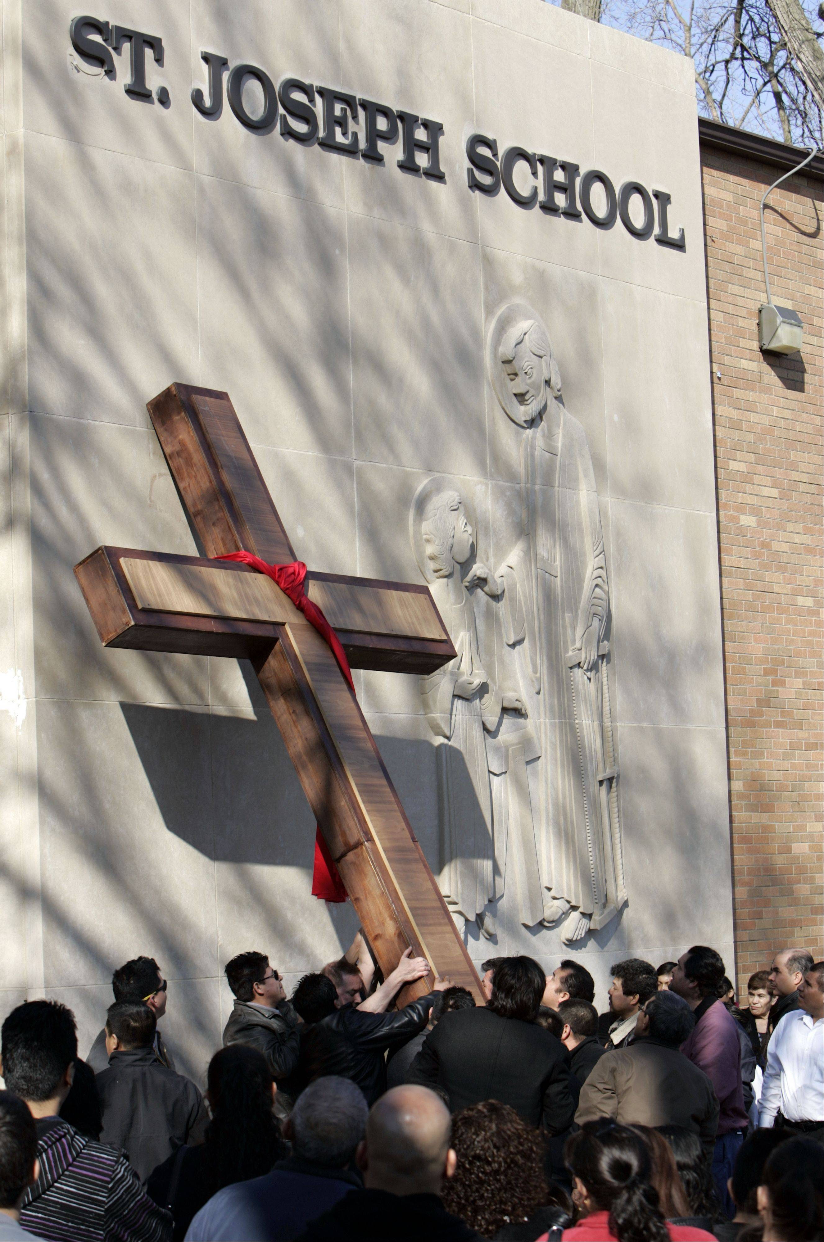 The cross is set upright at St. Joseph's during after the Good Friday procession through Elgin Friday.