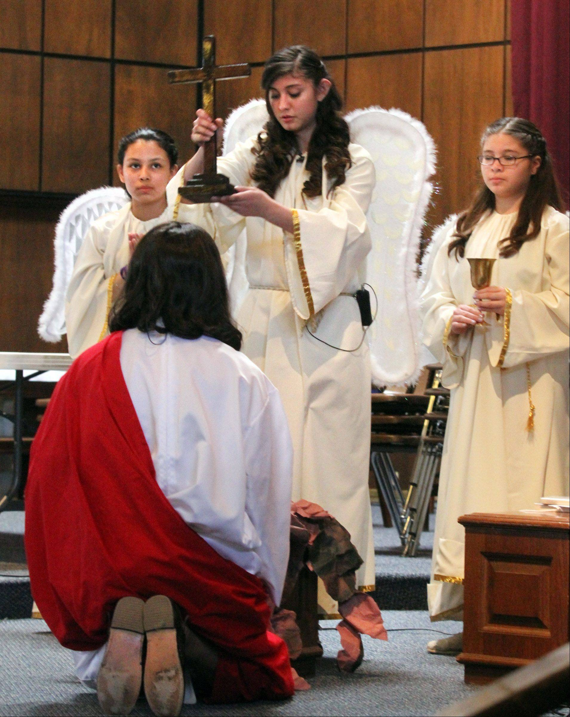 "An angel played by Mayela Correa, of Mundelein, speaks to Jesus played by Miguel Angel Correa (Mayela's father during ""Way of the Cross"" at Stanta Maria del Popolo Catholic Church in Mundelein on Friday."