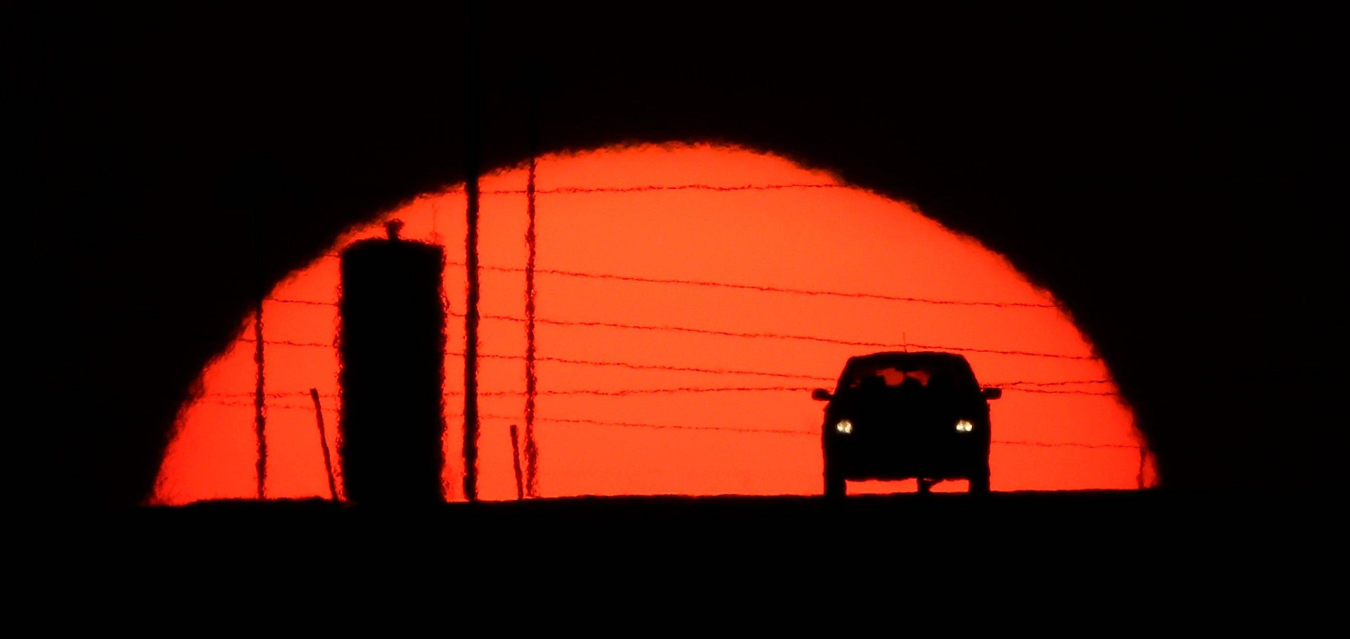A car is silhouetted against the setting sun as it travels along Interstate 70 Wednesday in Kansas City, Kansas.
