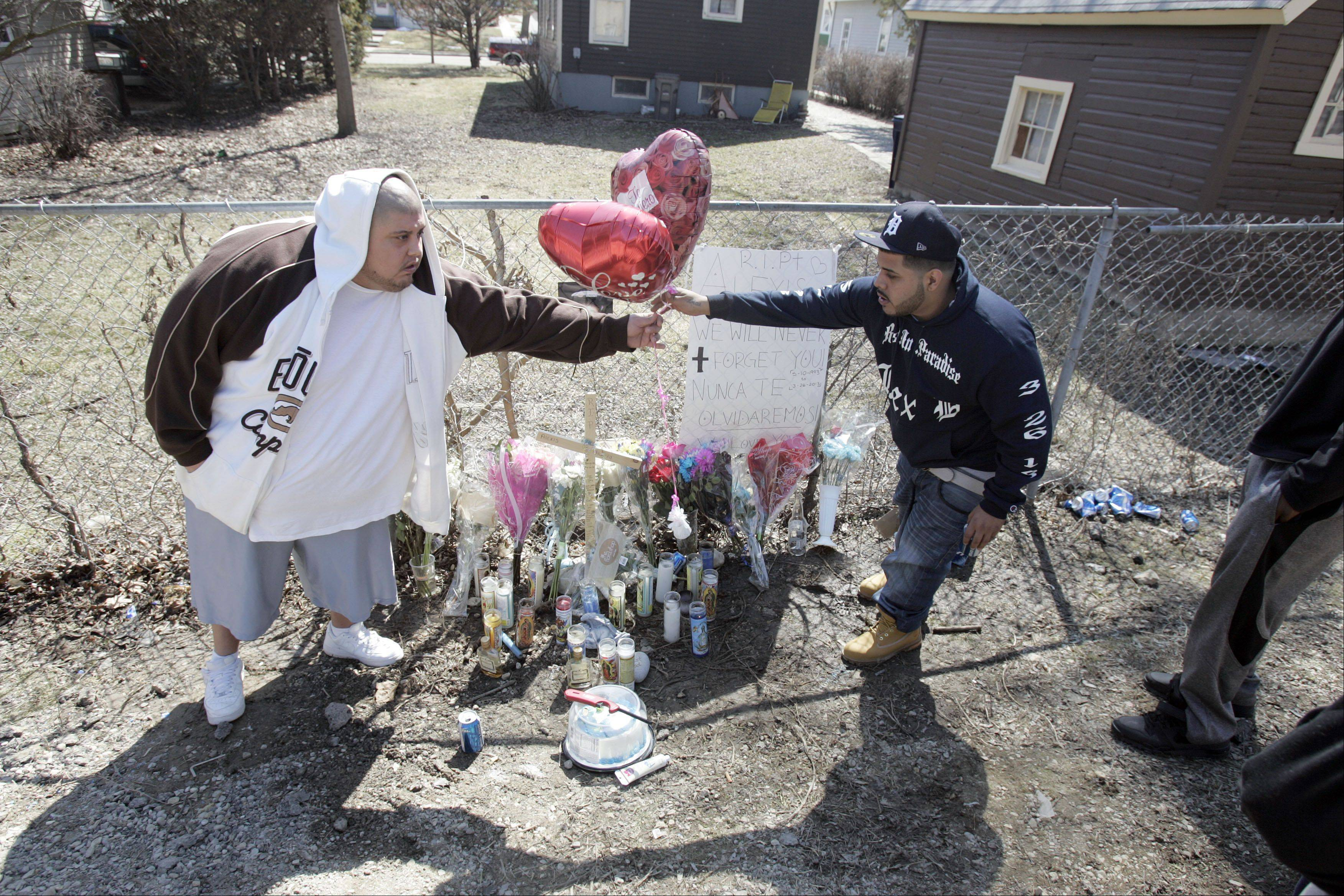 "Robert Trujillo, left, and Victor Anthony ""Vito"" Botti adjust some balloons at a memorial for their friend, 19-year-old Alexis Huerta, who was killed in a shooting Tuesday night in Elgin. The memorial is in the 200 block of Silver Court, where Huerta was found shot."