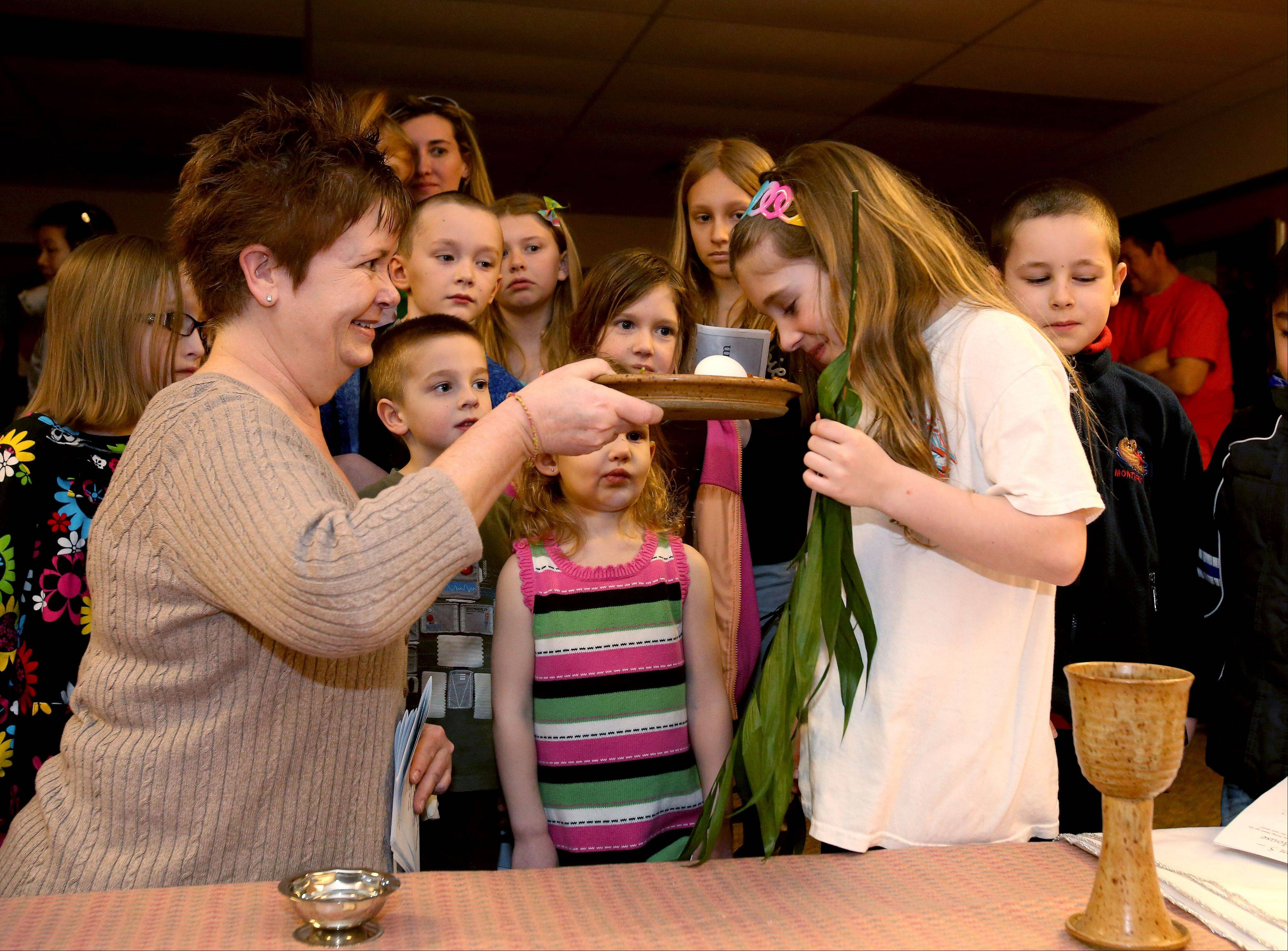 Cathy Fulgham asks Allison Anderson to smell the horseradish as she tells youngsters about Passover food during the Cross Walk at Alleluia! Lutheran Church in Naperville.