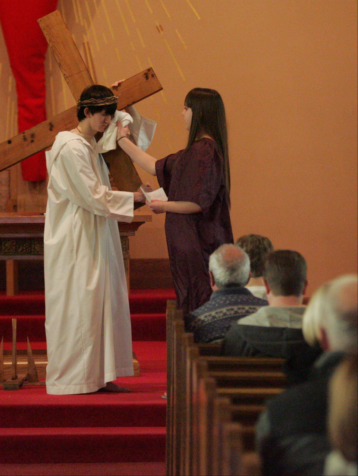 Veronica, portrayed by Aimee Frost, 15, wipes the face of Jesus, portrayed by T.J. Foley, 18, at the sixth station during a living Stations of the Cross Friday afternoon at St. Gall Catholic Church in Elburn. Both are from Elburn. The youth group at the church put the program together.