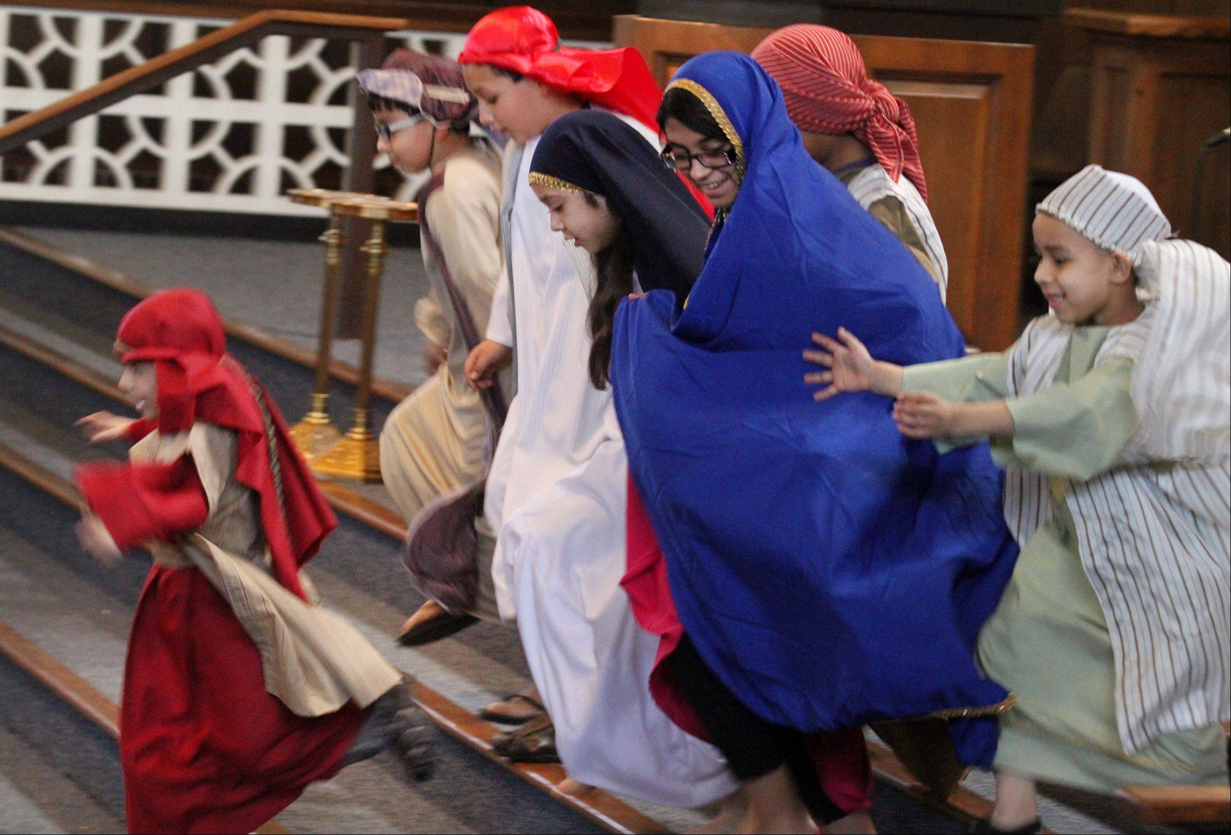 Children run to Jesus during Via Crucis, or Way of the Cross, at Santa Maria del Popolo Catholic Church in Mundelein on Friday.
