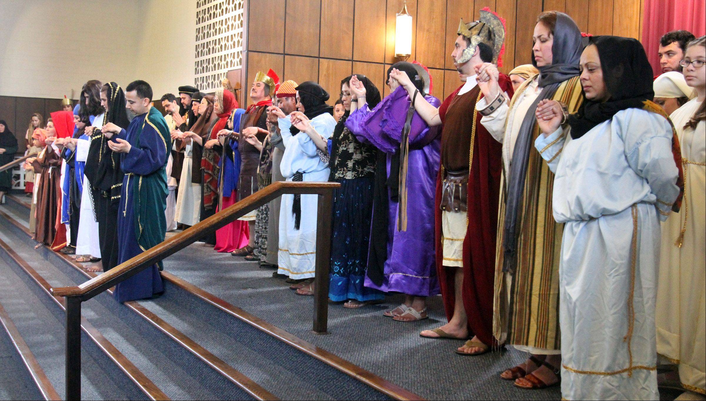 "The cast of ""Way of the Cross"" prays after performing at Santa Maria del Popolo Catholic Church in Mundelein on Good Friday."