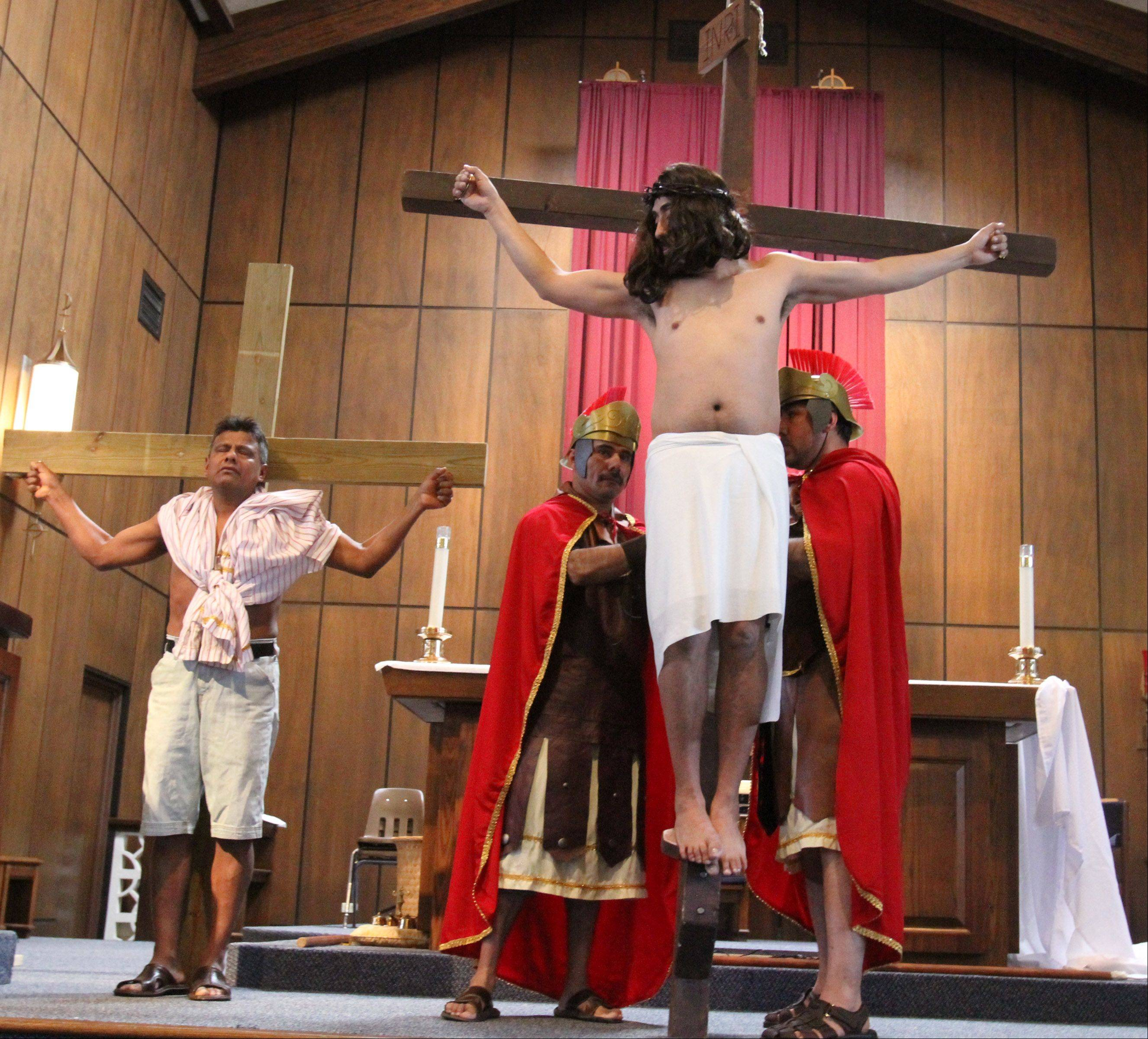Jesus, portrayed by Miguel Angel Correa, is placed on the cross by guards during the Spanish-language Via Crucis at Santa Maria del Popolo Catholic Church in Mundelein on Friday.