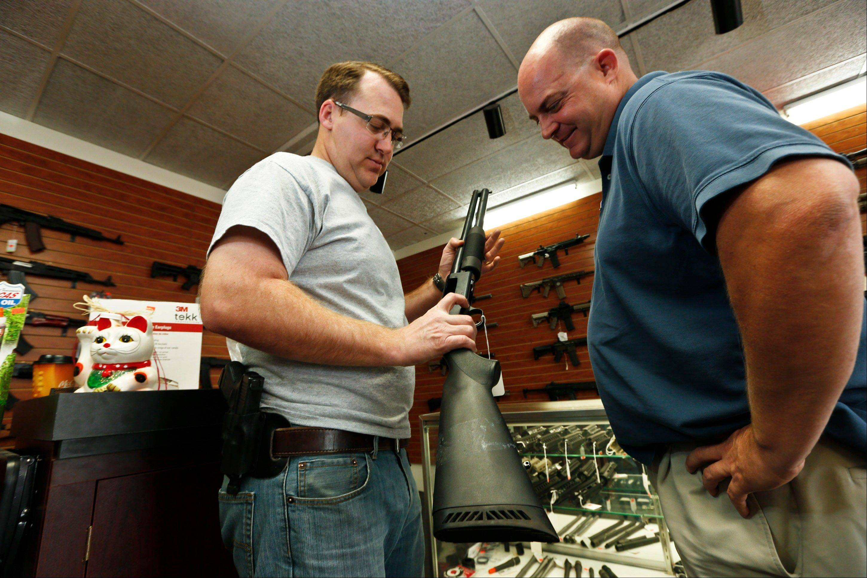 Black Weapons Armory store owner Tommy Rompel, left, shows former mayoral candidate Shaun McClusky, a shotgun Thursday at the Tucson, Ariz., store. The weapon is similar to those to be given away as part of a privately funded program he is launching to provide residents in crime-prone areas with free shotguns.