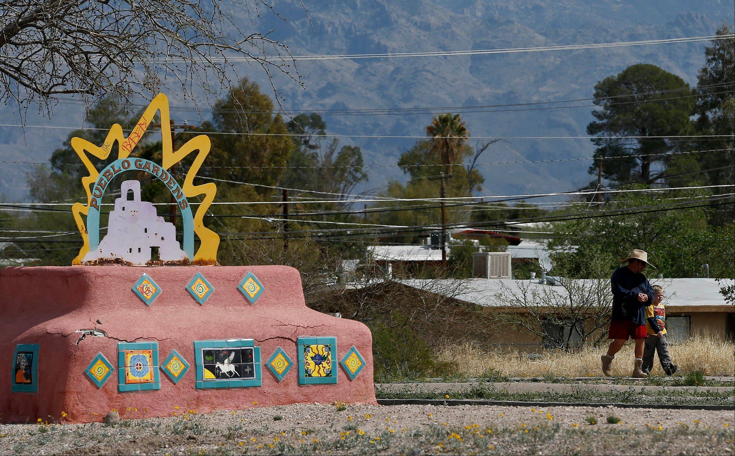 Residents of Pueblo Gardens walk past a sign Thursday for the Tucson, Ariz. development.