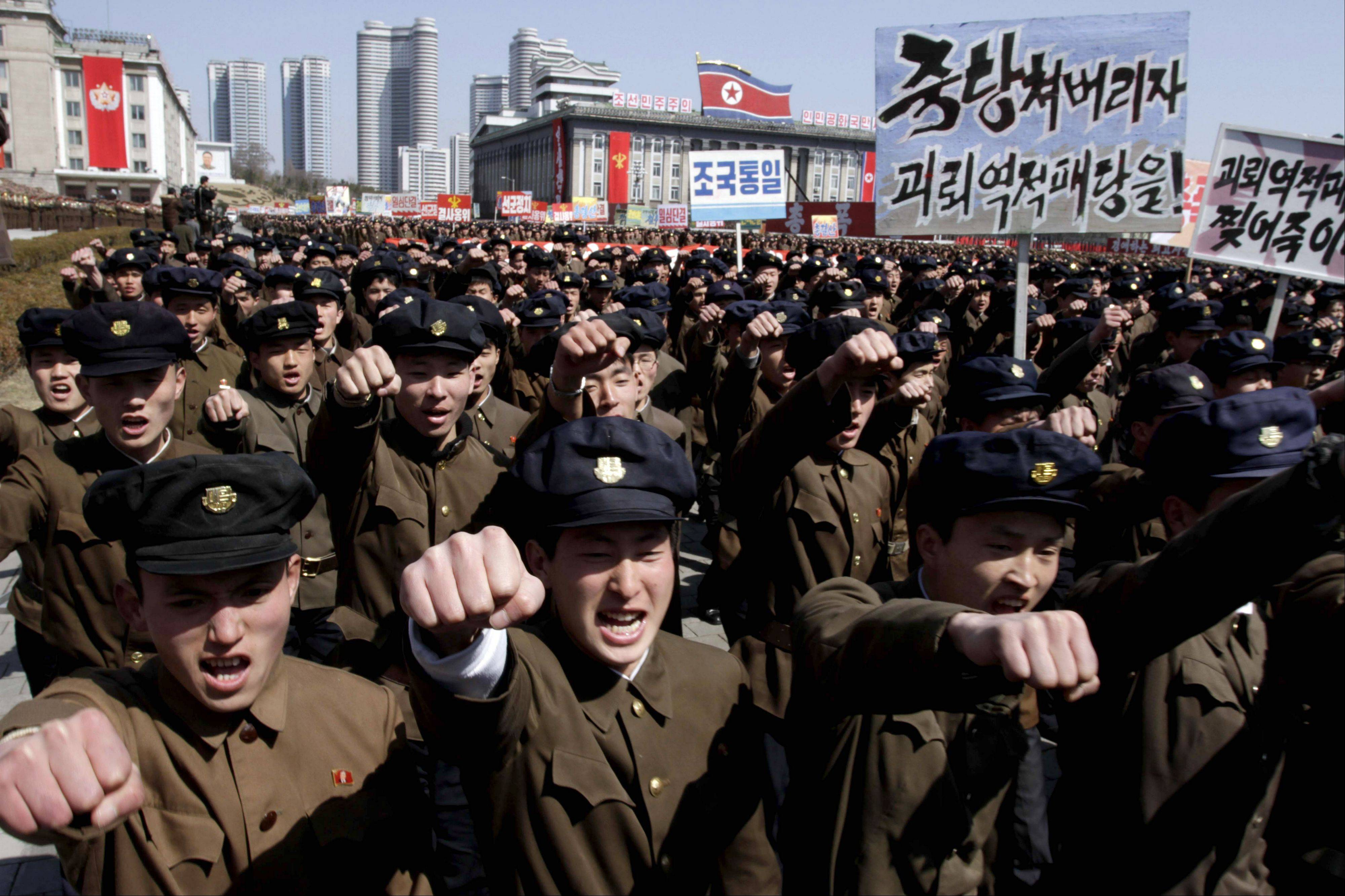 "University students punch the air Friday as they march through Kim Il Sung Square in downtown Pyongyang, North Korea. Tens of thousands of North Koreans turned out for the mass rally at the main square in Pyongyang in support of their leader Kim Jong Un's call to arms. Placards read: ""Let's crush the puppet traitor group"" and ""Let's rip the puppet traitors to death!"""