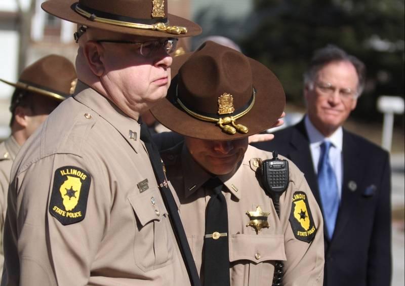 Illinois State Police Capt. Joseph Perez consoles Lt. Mark Karczewski after  Karczewski spoke during