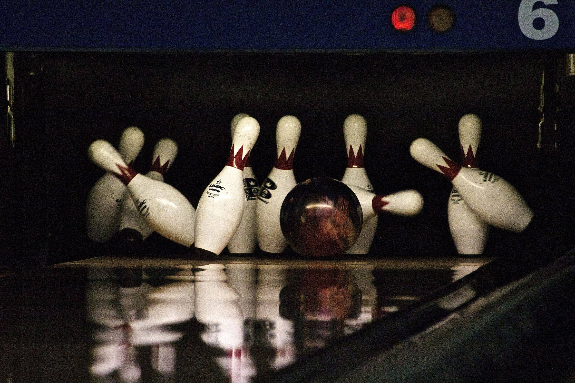 Bowling pins are caught in mid air after the ball strikes them.