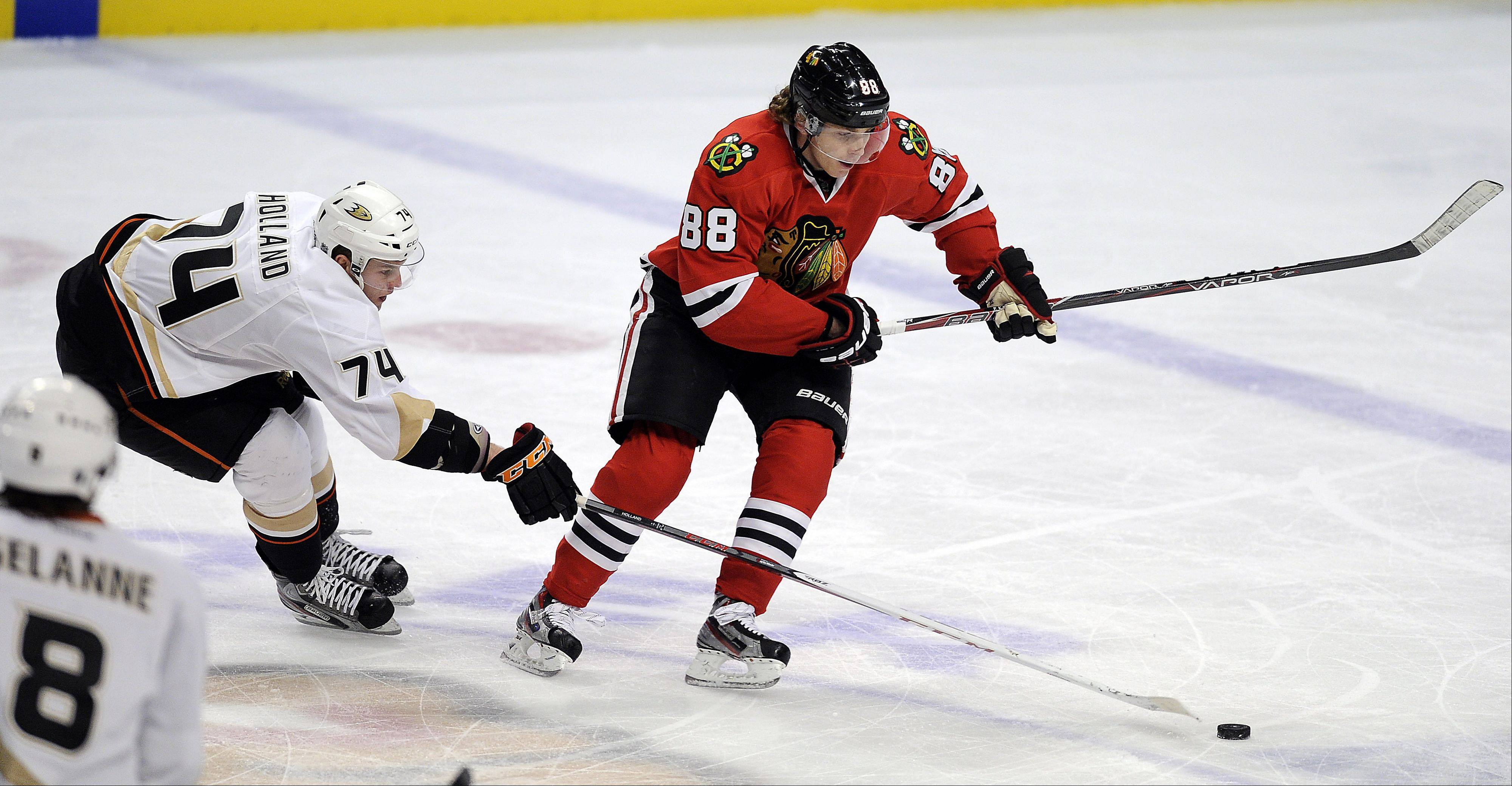 Mark Welsh/mwelsh@dailyherald.comBlackhawks Patrick Kane battles Anaheim's Peter Holland in the secind period at the United Center in Chicago on Friday.