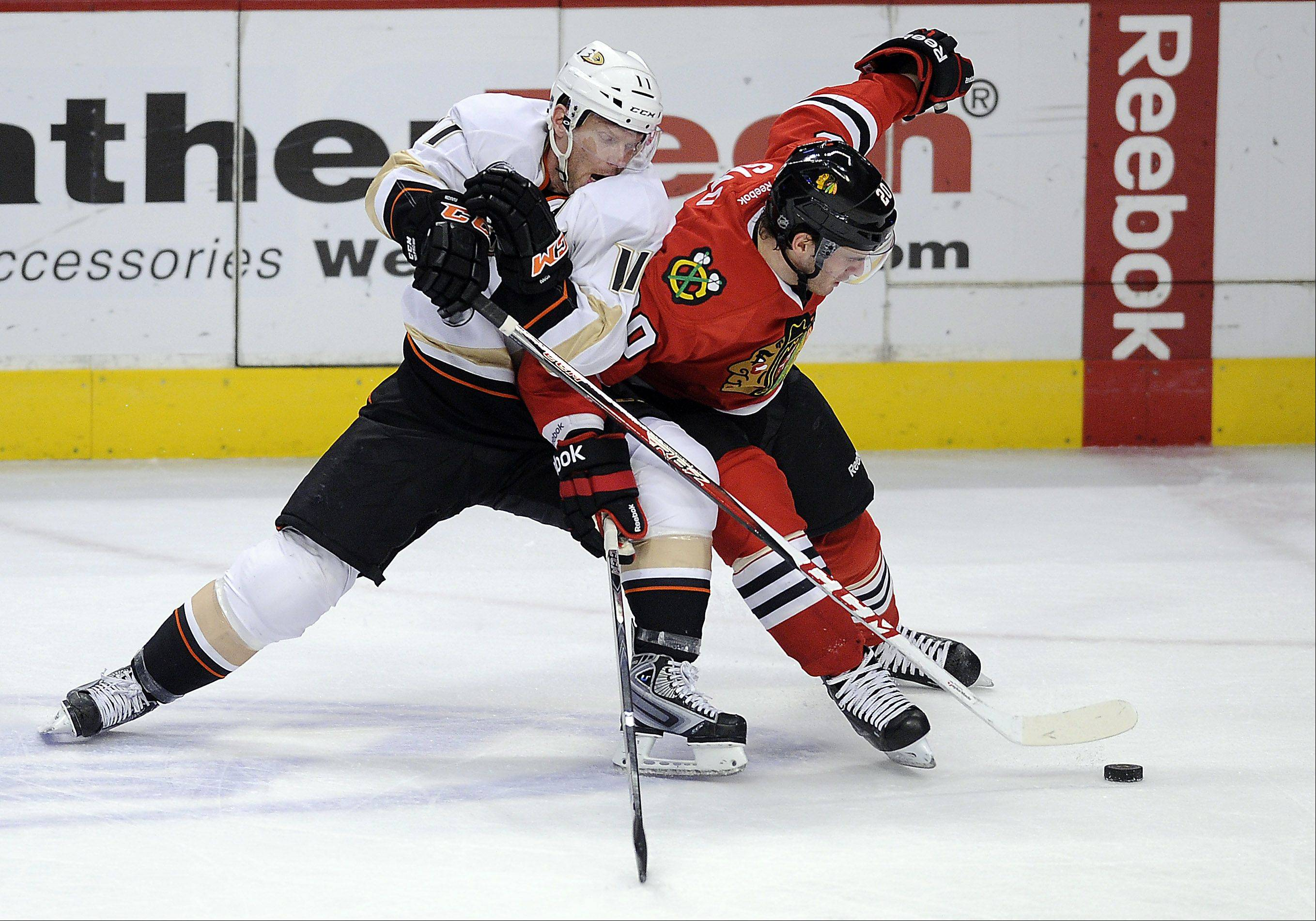 Mark Welsh/mwelsh@dailyherald.comBlackhawks Brandon Saad battles Anaheim's Saku Koivu in the second period for control of the puck at the United Center in Chicago on Friday.