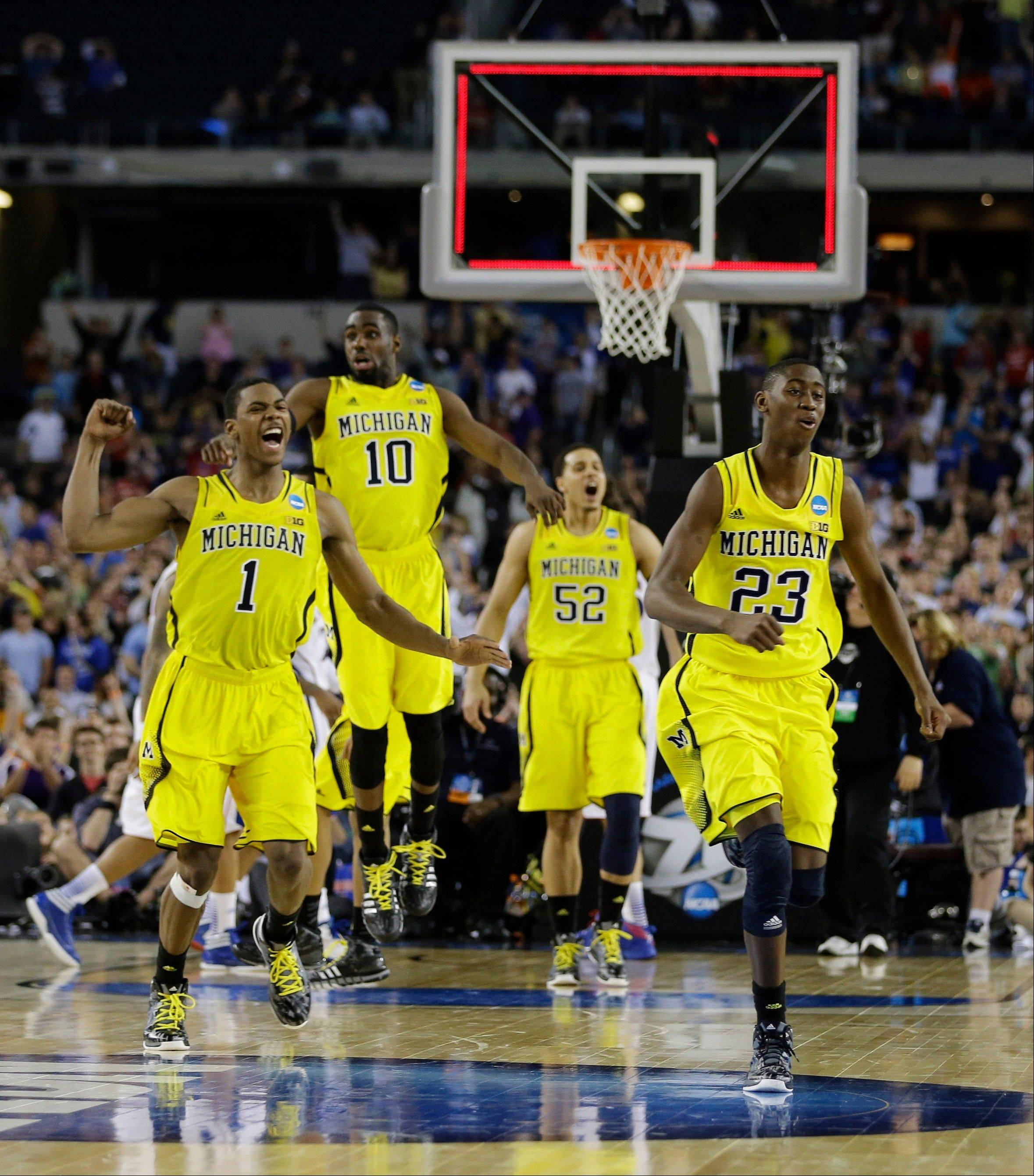 Michigan's Glenn Robinson III (1), Tim Hardaway Jr. (10), Jordan Morgan (52), Caris LeVert (23) celebrate after beating Kansas 87-85 in overtime of a regional semifinal game in the NCAA college basketball tournament, Friday, March 29, 2013, in Arlington, Texas.
