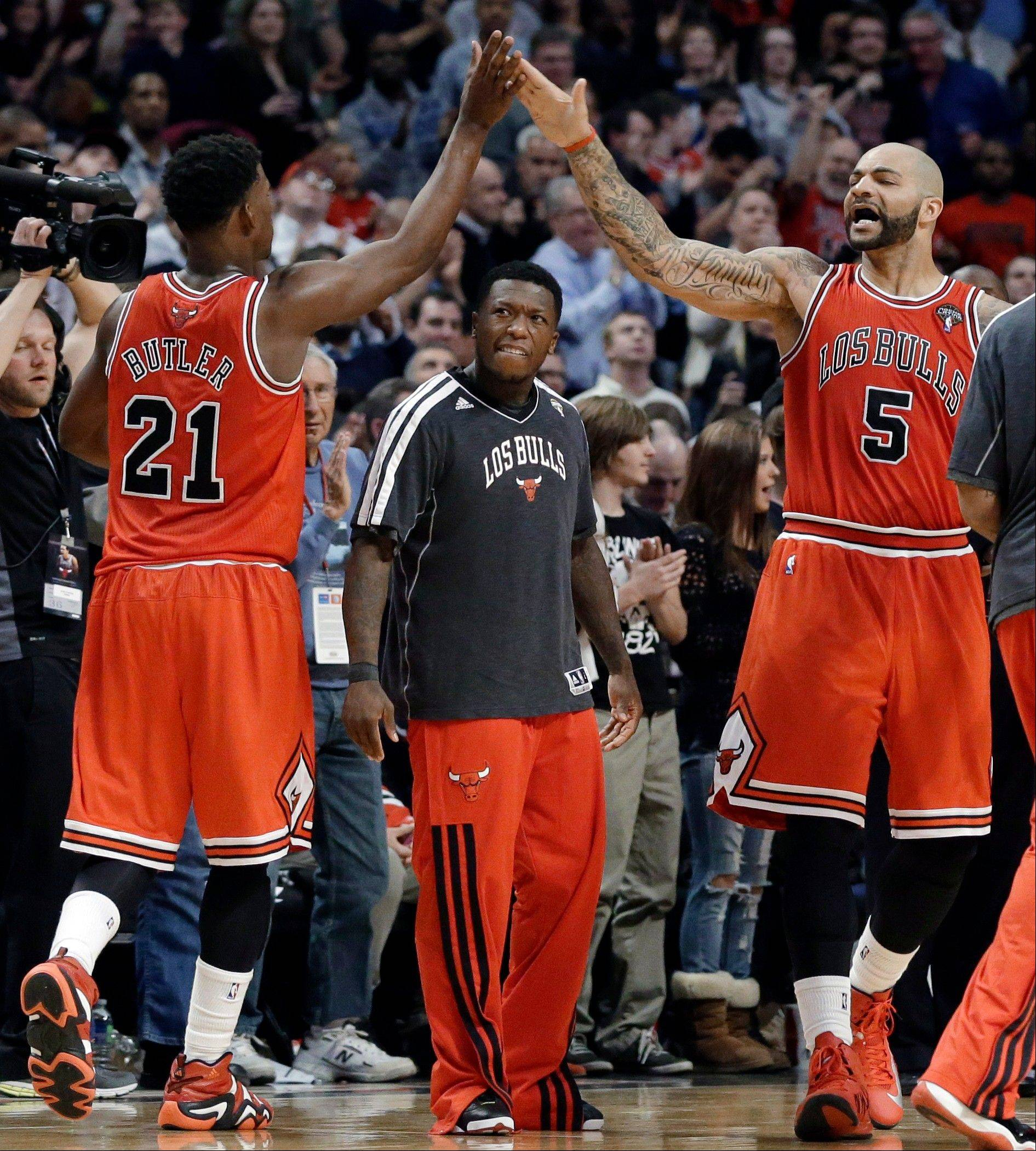 Chicago Bulls guard Jimmy Butler, left, celebrates with forward Carlos Boozer after scoring a basket, as Nate Robinson, center, watches during the second half of an NBA basketball game against the Miami Heat in Chicago on Wednesday, March 27, 2013. The Bulls won 101-97, ending the Heat's 27-game winning streak.