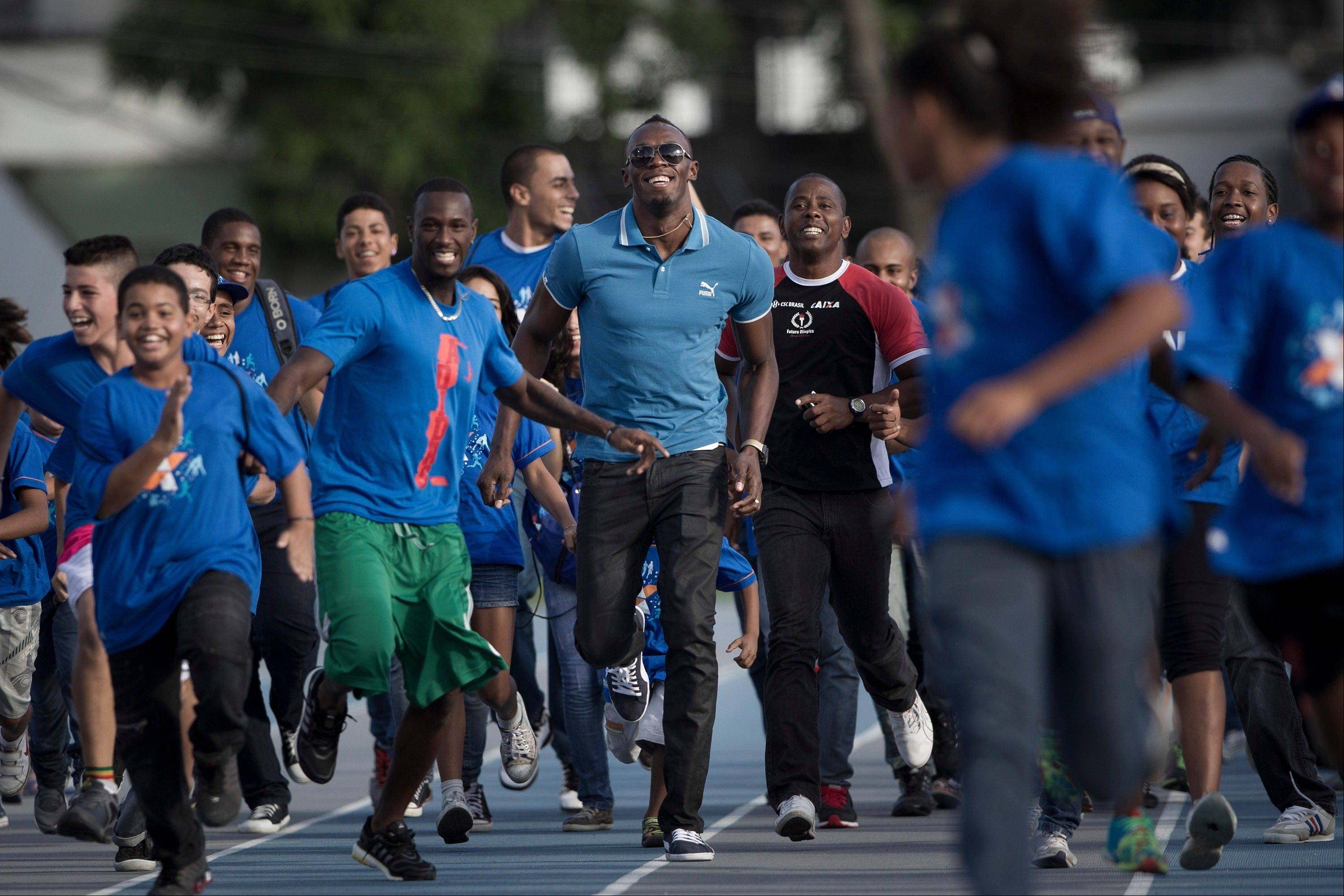 Jamaican Olympic gold medalist Usain Bolt, center, and sprinter Daniel Bailey, from Antigua and Barbuda, center left, run with young athletes during their visit to the Projeto Futuro Olimpico or Olympic Future Project in Rio de Janeiro, Brazil, Thursday, March 28, 2013. The Olympic Future Project promotes the practice of sports and healthy living, targeting the low-income populations of the inner city.