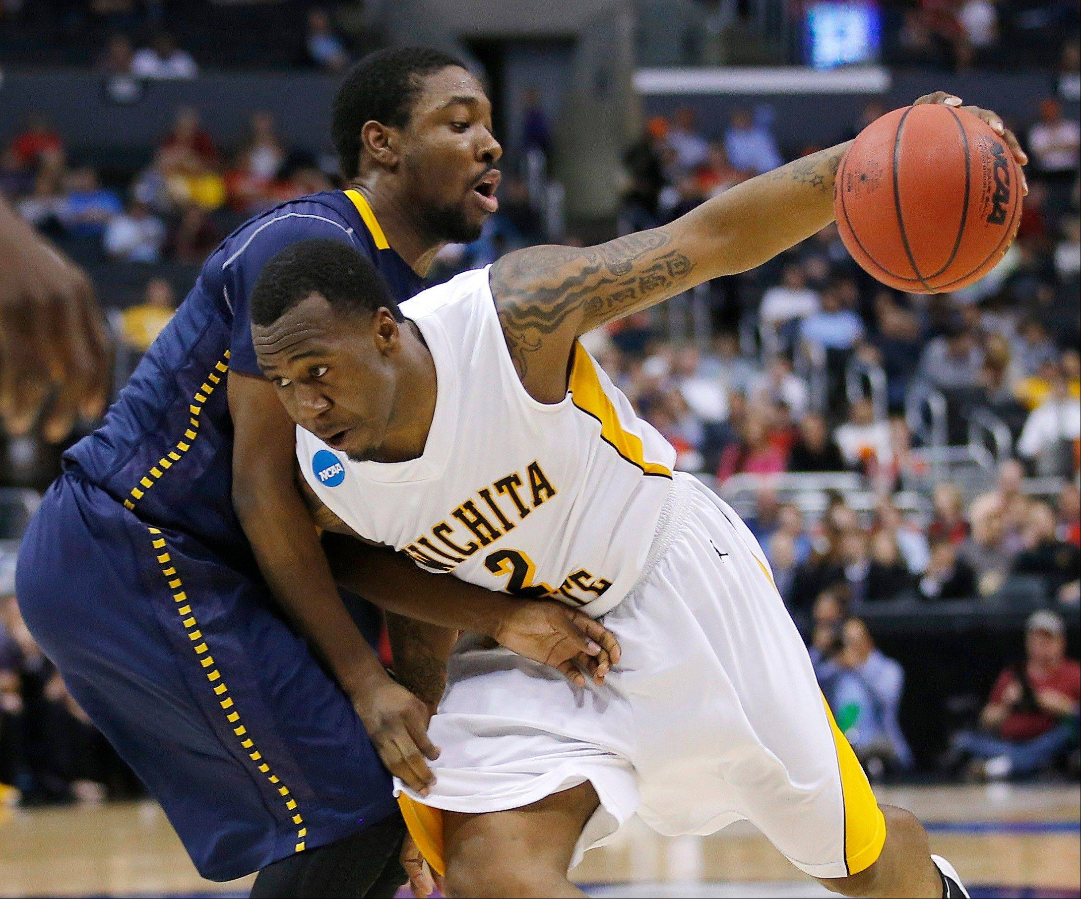 La Salle guard Sam Mills, left, defends Wichita State guard Malcolm Armstead during the second half of a West Regional semifinal in the NCAA men's college basketball tournament, Thursday, March 28, 2013, in Los Angeles.