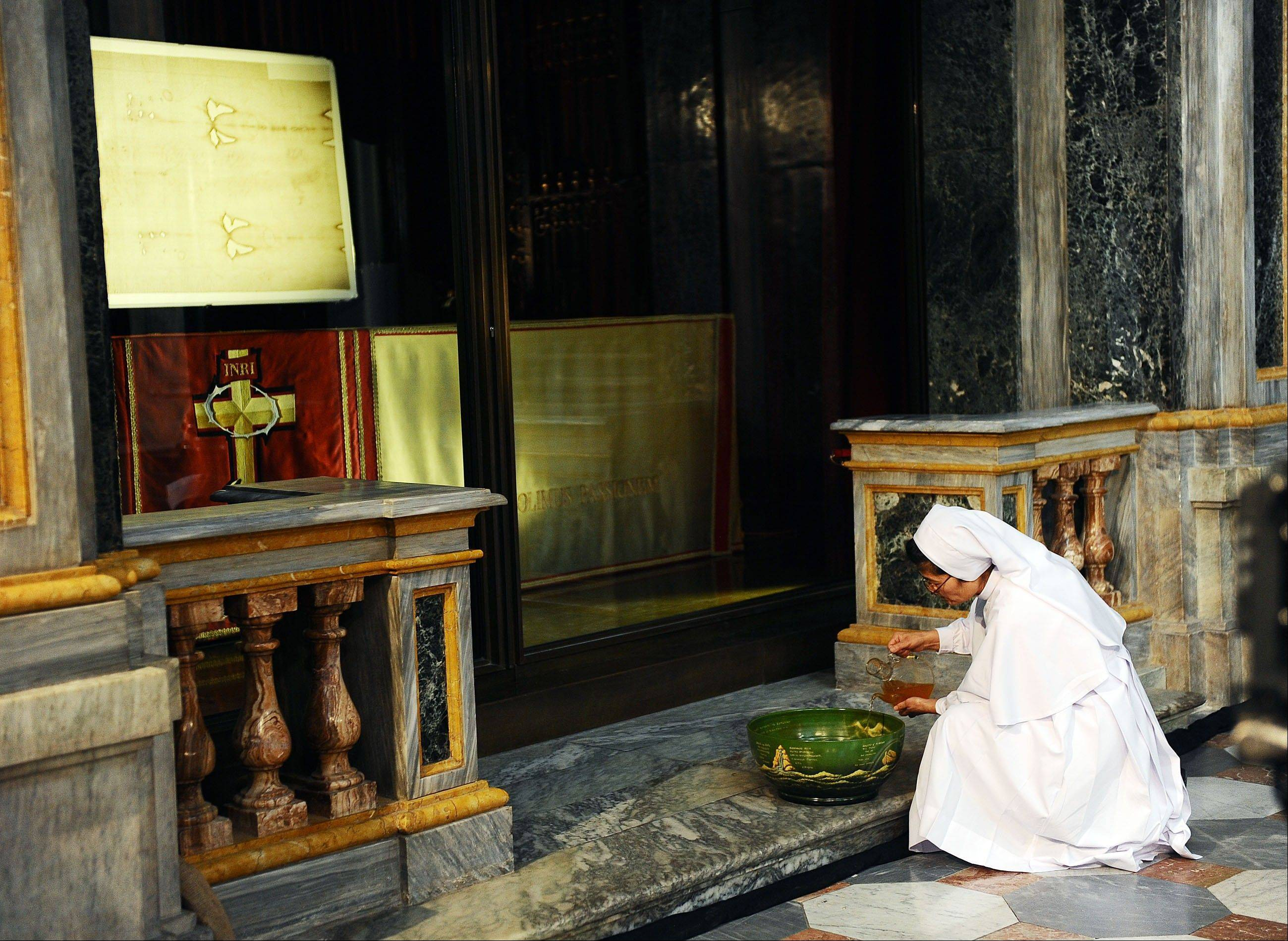 A nun pours oil in front of the Shroud of Turin Saturday that went on display for a special TV appearance, at the Turin cathedral, Italy. The Shroud went on display amid new research disputing claims it�s a medieval fake and purporting to date the linen some say was Jesus� burial cloth to around the time of his death.