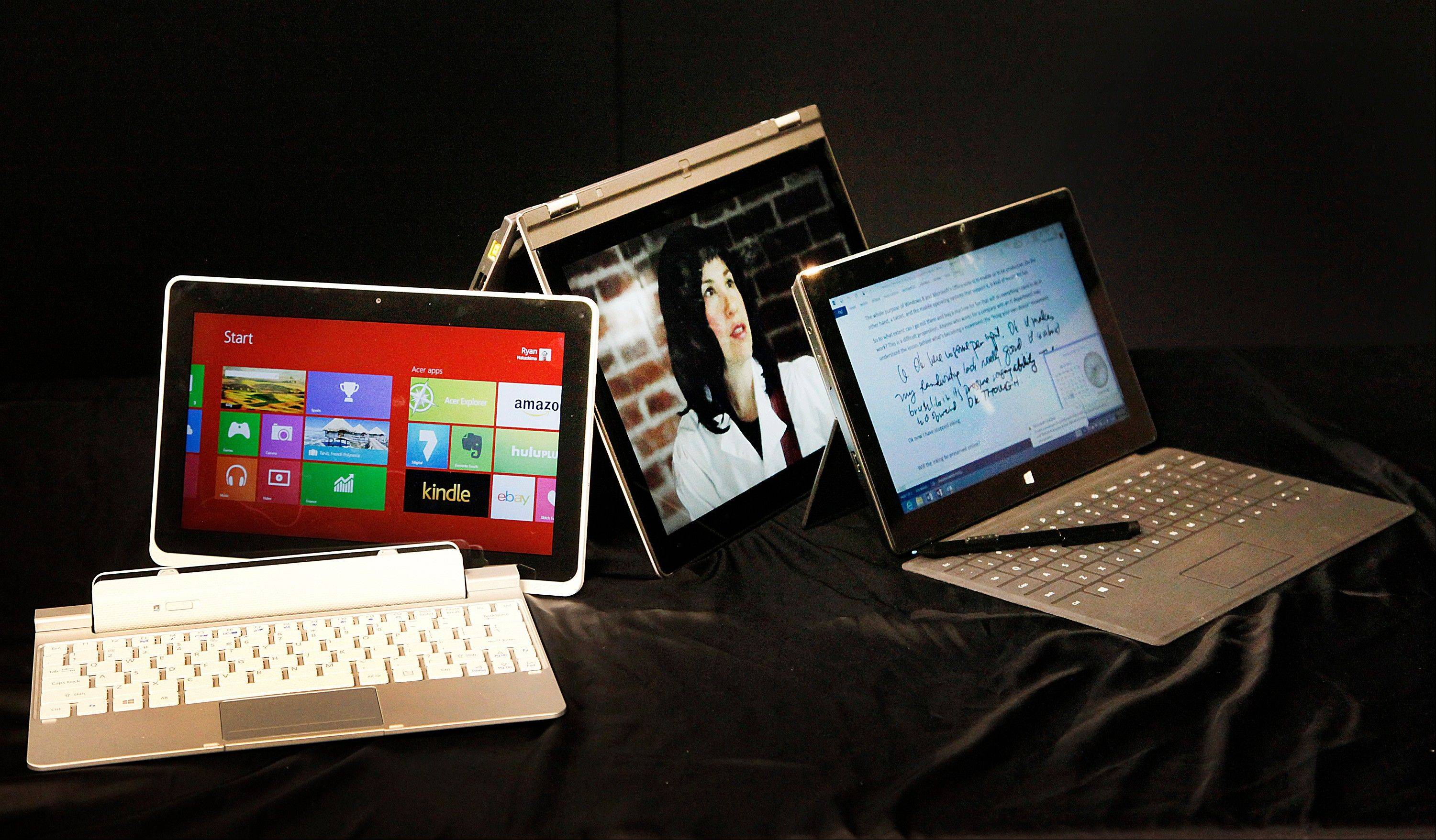 This photo taken Tuesday March 26, 2013 shows three hybrid computers running on Windows 8, from left to right, the Iconia W510 by Acer, the Yoga 13 by Lenovo and the Surface Pro by Microsoft, in Los Angeles. Since Windows 8ís debut in October, there have been a range of hot-looking devices that try to combine elements of tablets and traditional PCs.
