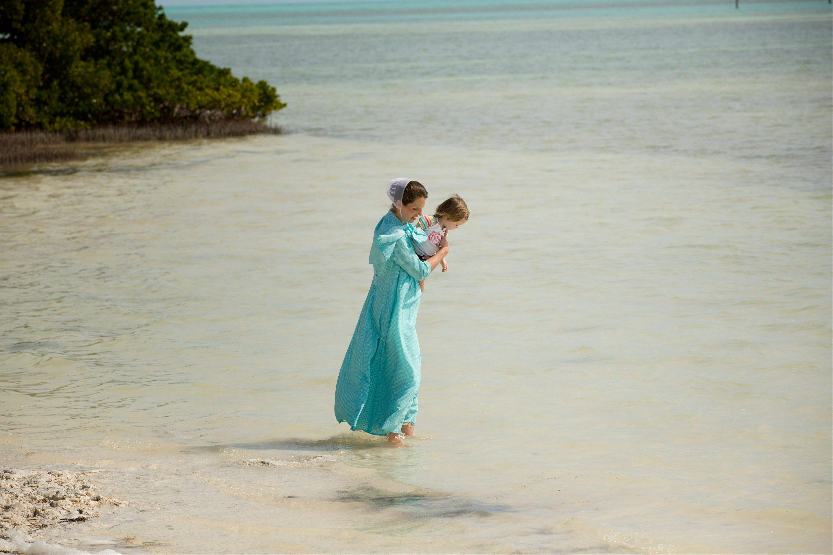 A visitor and her daughter wade in the waters of Anne's Beach near Islamorada, Fla.