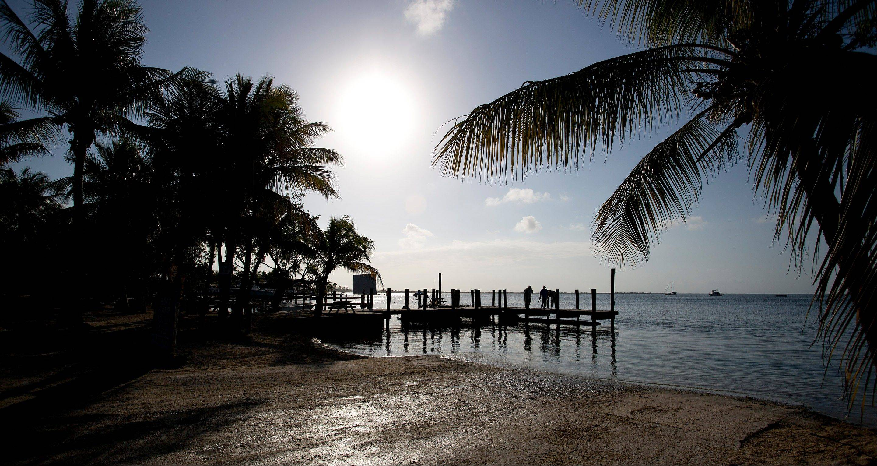 Visitors to Key Largo, Fla., stand on a pier and watch the sunset. If you're heading south into the Keys from the Miami or Fort Lauderdale areas, Key Largo is the first island you hit.