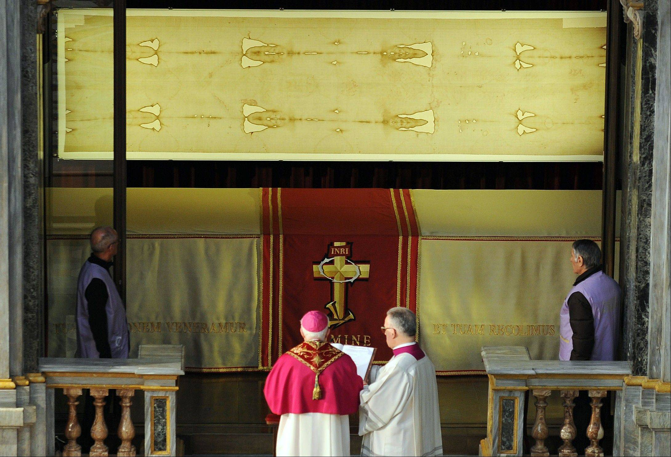 Archbishop of Turin Cesare Nosiglia, second left, watches the Shroud of Turin, on display for a special TV appearance Saturday.