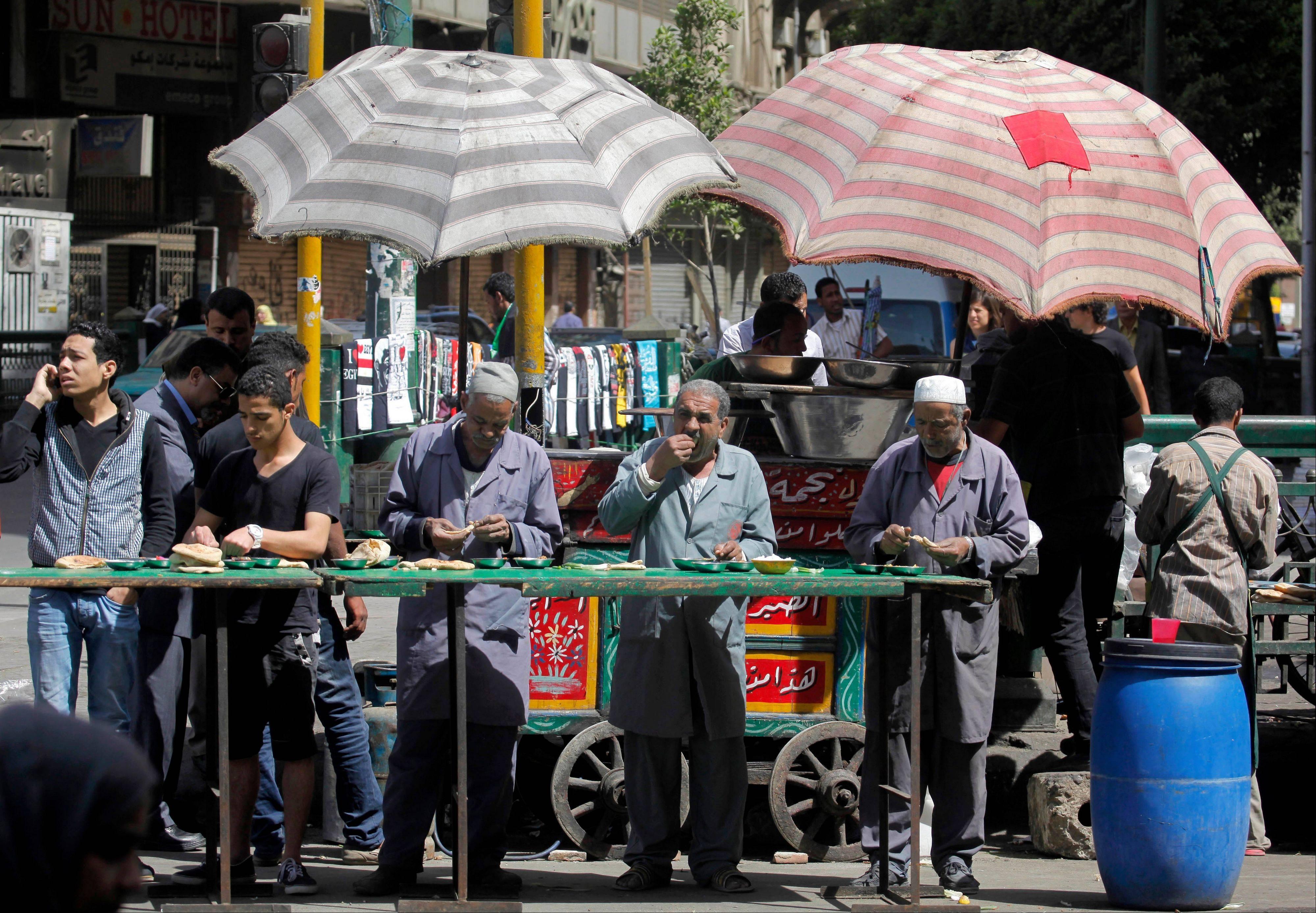 Egyptians eat foul, or fava beans, at an open-air cart restaurant Saturday in Cairo. Egypt has faced near-constant turmoil in the more than two years since longtime, authoritarian leader Hosni Mubarak was overthrown in a revolt.