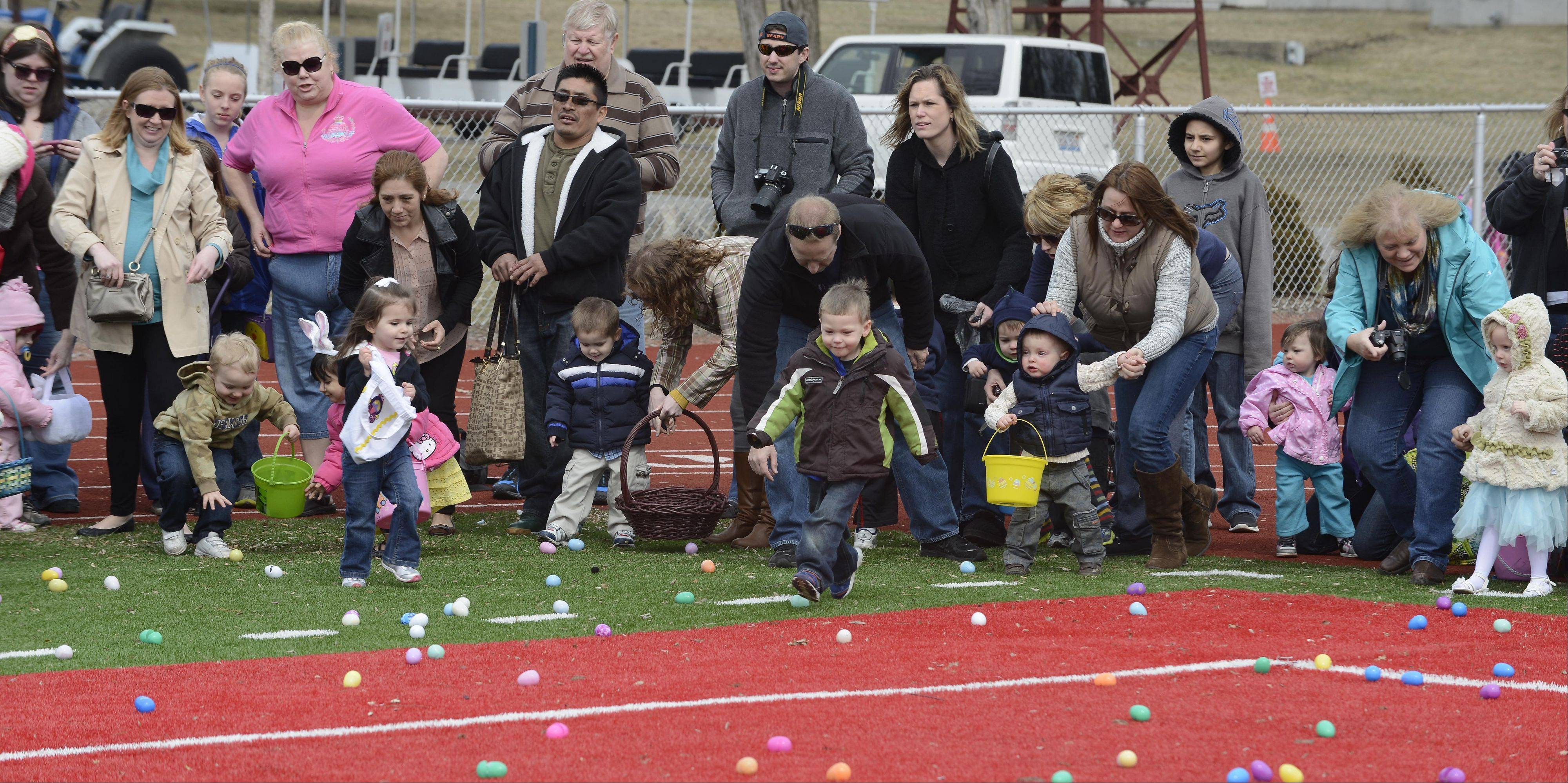 Children hurry to gather eggs during Saturday's Easter egg hunt at Mooseheart.