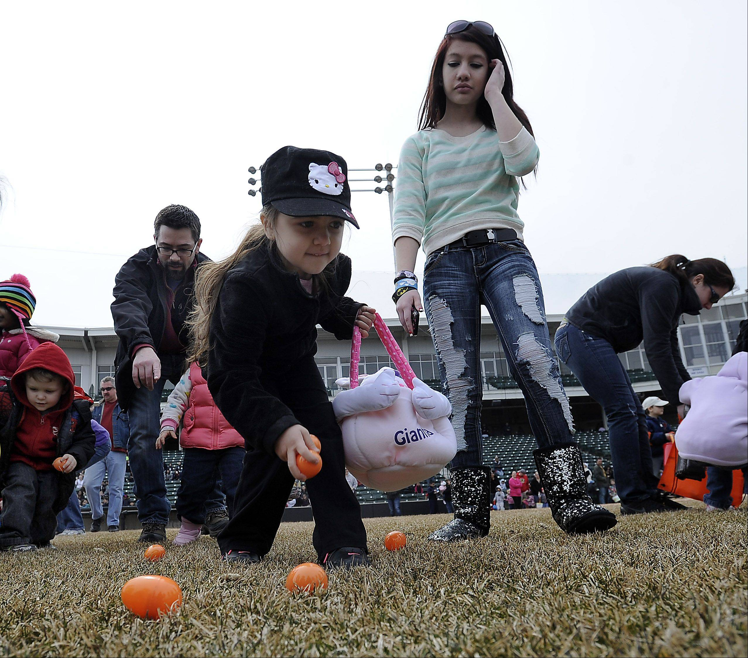 Gianna Balsamo,4, of Schaumburg and her helper Kaitin Agron,15, scoop up as many Easter eggs as possible in the mad rush at the Schaumburg Boomers 2nd annual Easter egg hunt on Saturday.